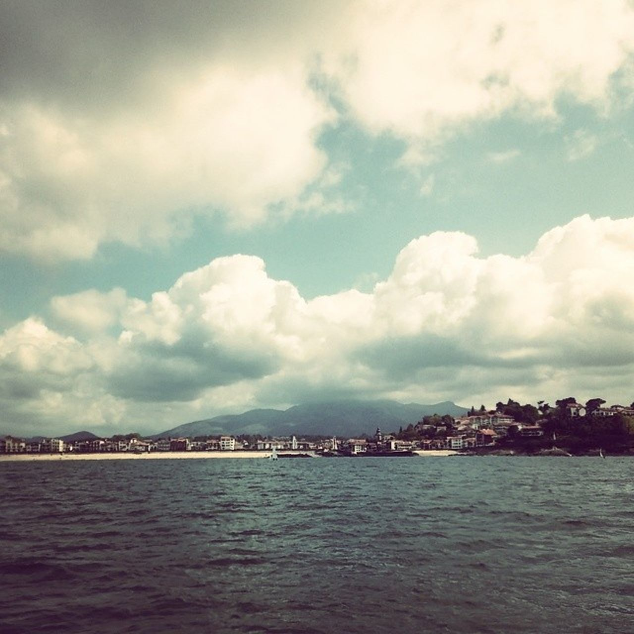 waterfront, water, sky, sea, cloud - sky, cloudy, scenics, tranquil scene, cloud, tranquility, beauty in nature, nature, rippled, built structure, building exterior, river, architecture, outdoors, day, city