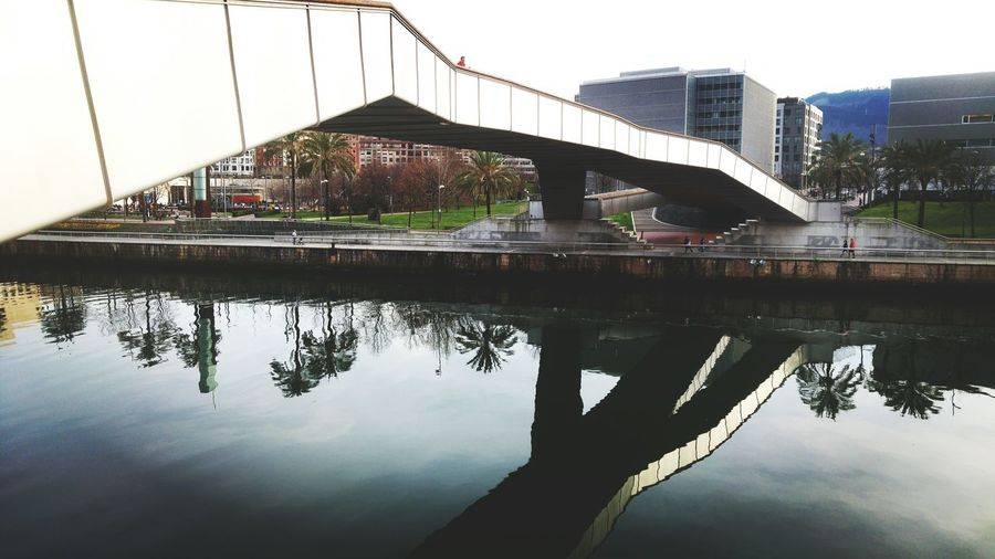 Reflection Architecture Water Bridge - Man Made Structure Built Structure Building Exterior City Outdoors Bilbao Palm Tree Riverside University Of Deusto SPAIN River Deusto Architecture City Reflection Connection Cloud - Sky Outdoor Spring Springtime Live For The Story The Architect - 2017 EyeEm Awards BYOPaper!