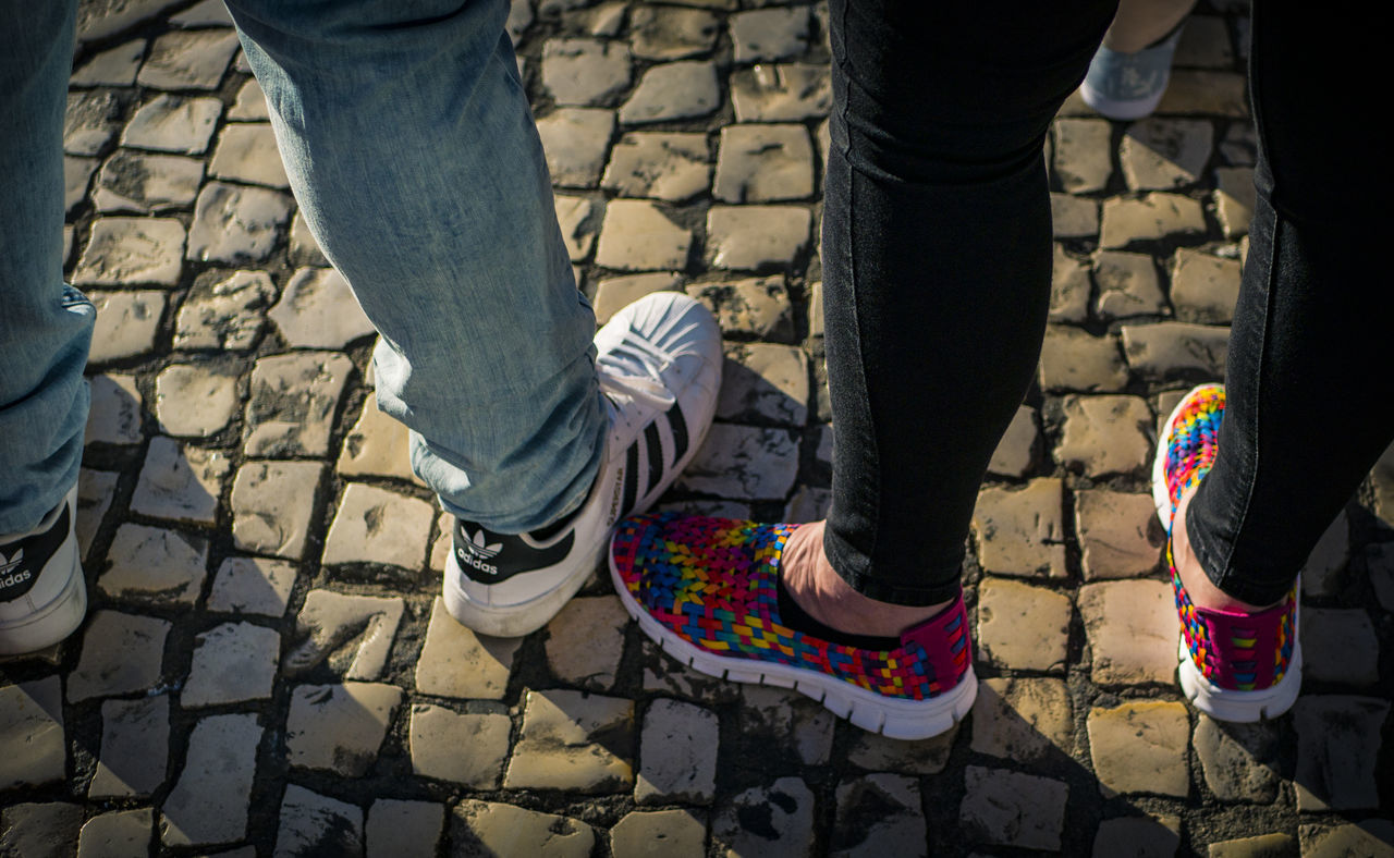 low section, human leg, shoe, standing, real people, cobblestone, lifestyles, day, two people, human body part, togetherness, outdoors, shadow, men, leisure activity, sunlight, women, bonding, adult, people