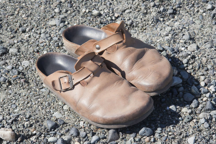 Old Clogs on the Rocks Aging Aging Process Beautyofdecay Brown Casual Clothing Clogs Close-up Decay Dirt Road Fashion Gravel Leather No People Old Old-fashioned Outdoors Pair Poverty Retro Retro Styled Run-down Shoe The Past Two Objects Wrinkles