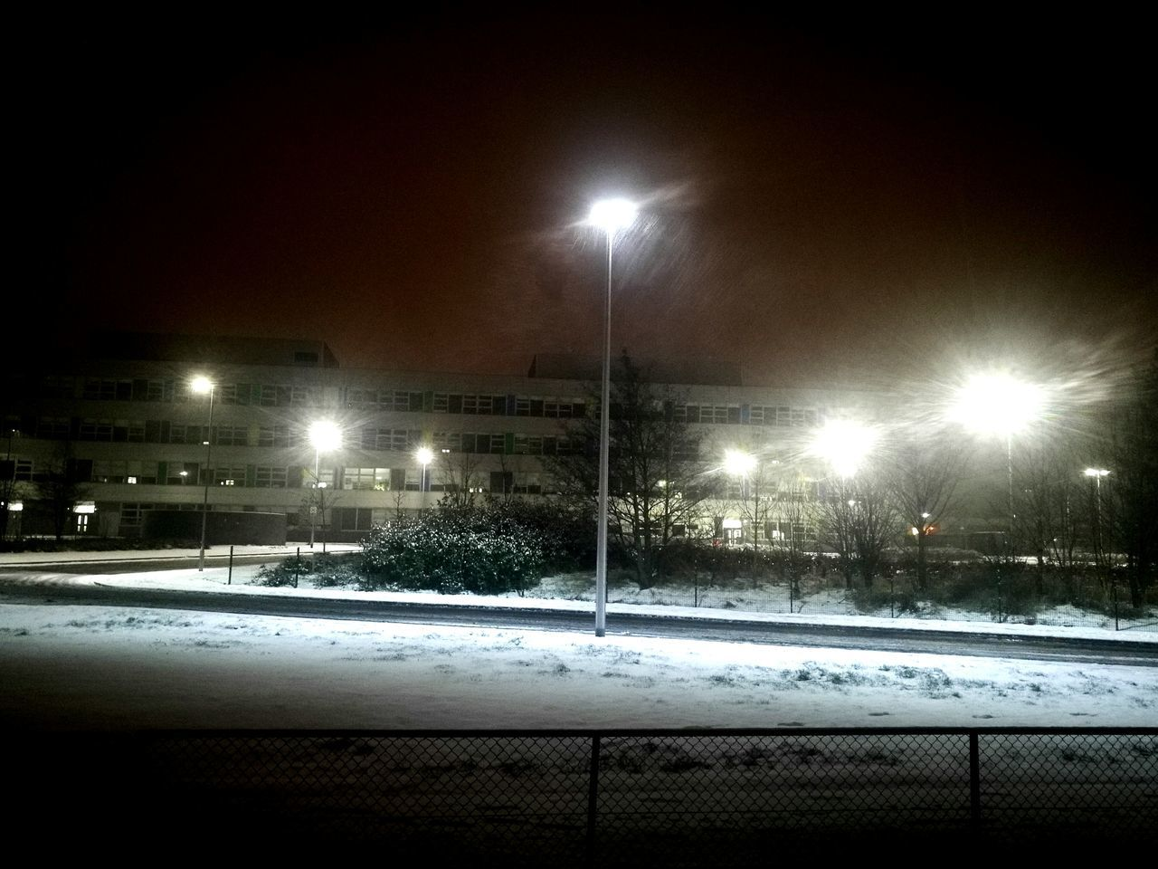 illuminated, night, snow, winter, cold temperature, street light, lighting equipment, weather, floodlight, no people, outdoors, building exterior, built structure, snowing, architecture, nature, sky, sport, ice rink