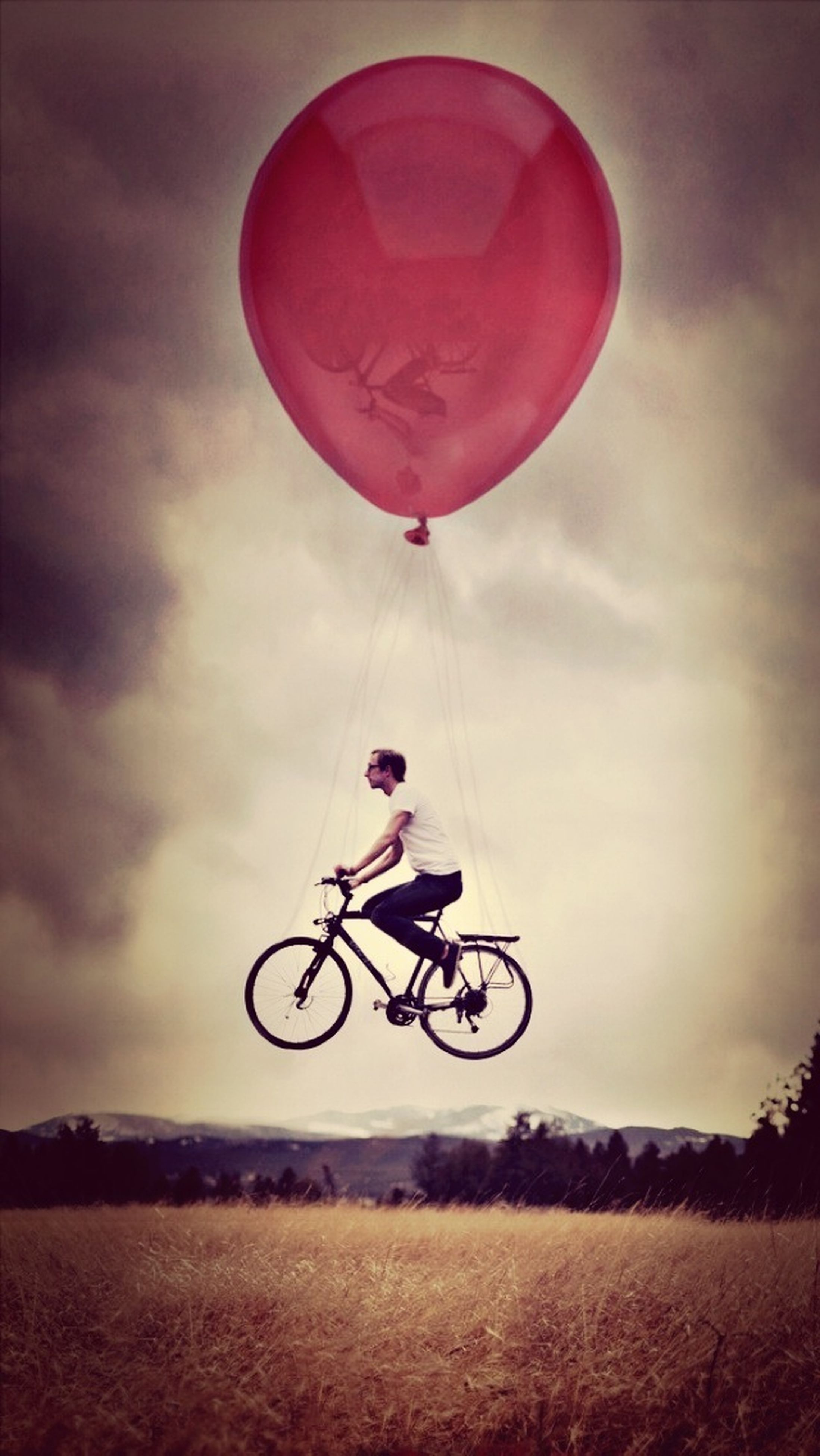 transportation, bicycle, sky, leisure activity, lifestyles, mode of transport, land vehicle, sport, cloud - sky, mid-air, riding, extreme sports, men, full length, adventure, cycling, parachute