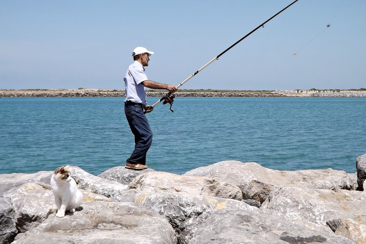 Adult Casual Clothing Day Dog Domestic Animals Fishing Fishing Pole Fishing Rod Fishing Tackle Full Length Holding Horizon Over Water Mammal Men Nature One Animal One Person Outdoors People Pets Real People Sea Sky Standing Water