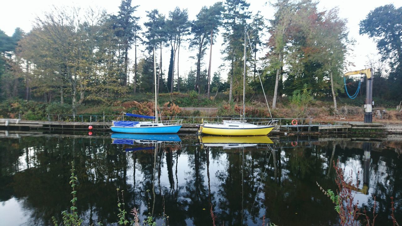 The twins little boats! Nautical Vessel Tree Water Transportation Mode Of Transport Reflection Moored Lake Outdoors Boat Nature Scenics Sky No People Tranquility Day Beauty In Nature Pedal Boat Antrim Lough Antrim Lough Northern Ireland Beauty In Nature Yellow Blue