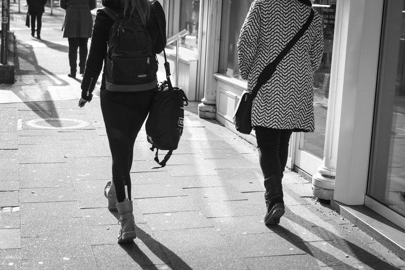 ESSEN, GERMANY - JANUARY 25, 2017: Two unidentifed ladies rush along the Rüttenscheider Straße in their winter boots Architectue Black & White Boots Bright Light Essen, Germany Leg Ouddoor People Sunny Urban Winter Women