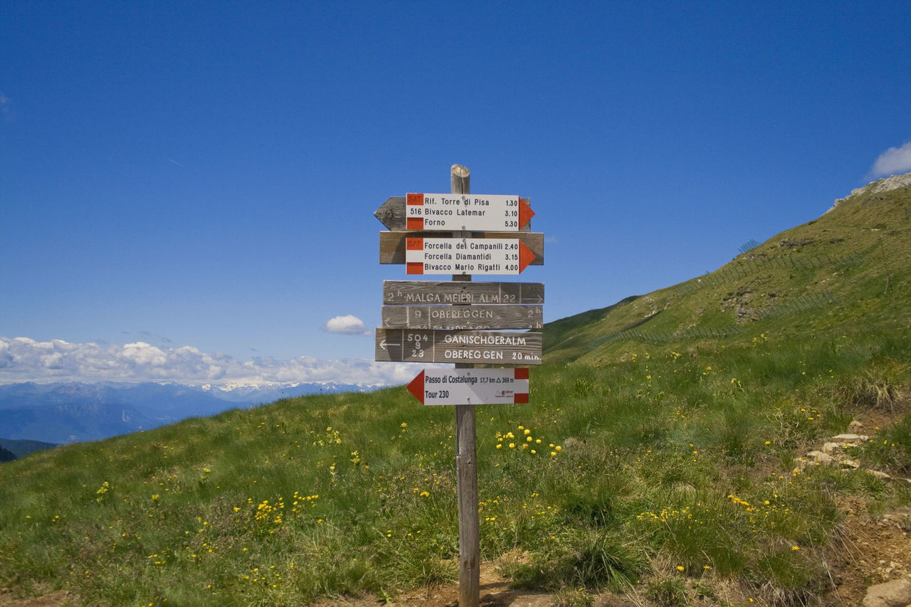 information sign on landscape against clear sky Alto Adige Beauty In Nature Blue Clear Sky Communication Day Grass Green Color Growth Landscape Mountain Mountain Range Mountain View Nature No People Outdoors Panoramic Photography Plant Scenics Sky Tranquil Scene Tranquility