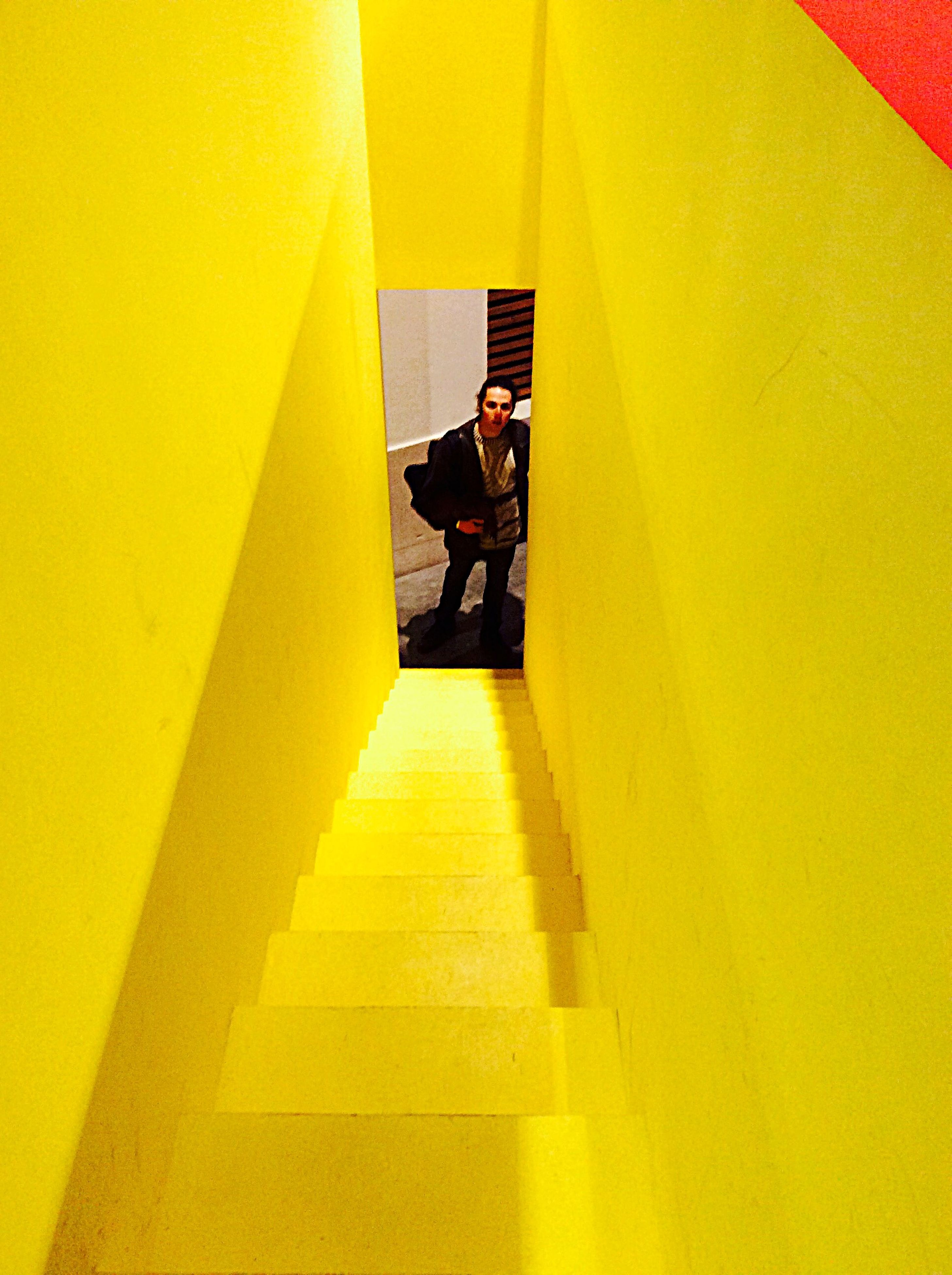 indoors, yellow, men, steps, walking, person, high angle view, stairs, staircase, narrow, vibrant color, convenience, architectural feature, modern, moving up, day, hand rail, corridor