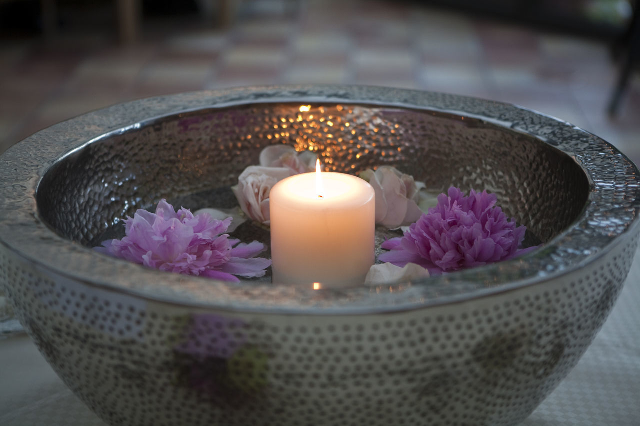 candle, flame, flower, burning, spirituality, tea light, close-up, petal, religion, aromatherapy, no people, indoors, focus on foreground, purple, scented, heat - temperature, freshness, illuminated, spa treatment, nature, fragility, beauty in nature, water, flower head, beauty spa, day