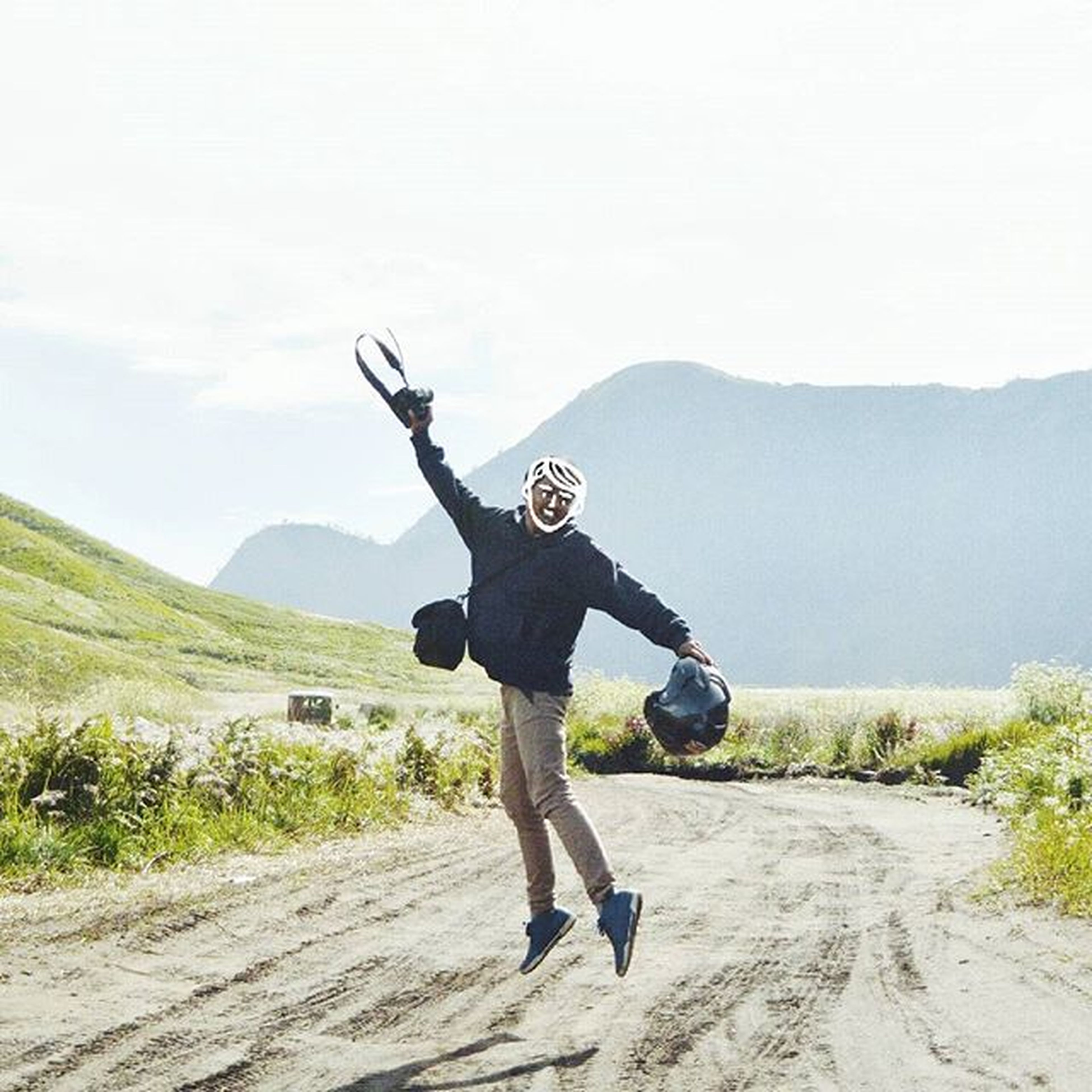 full length, lifestyles, leisure activity, casual clothing, young adult, jumping, mid-air, skill, landscape, clear sky, arms outstretched, freedom, mountain, sport, healthy lifestyle, holding, sky, person