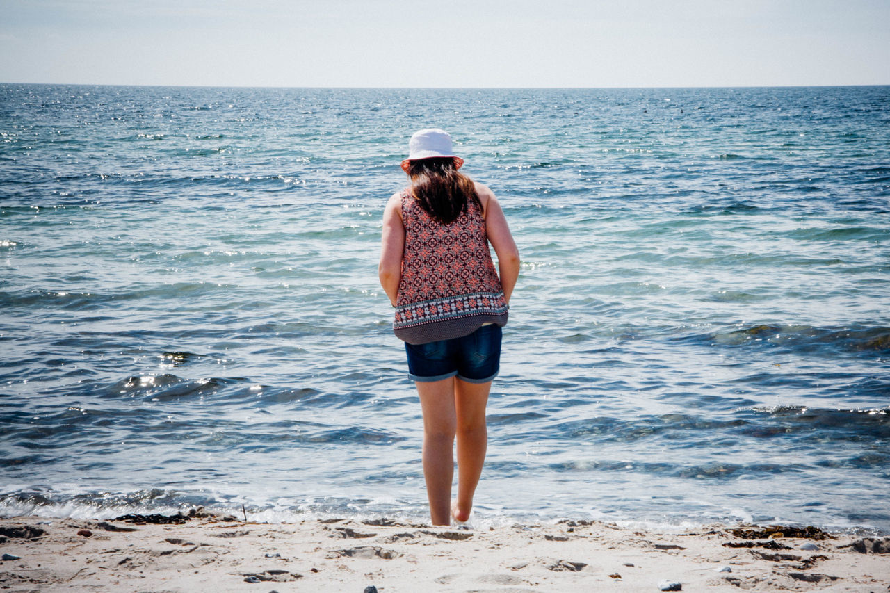 Rear View Of Woman Standing At Sea Shore