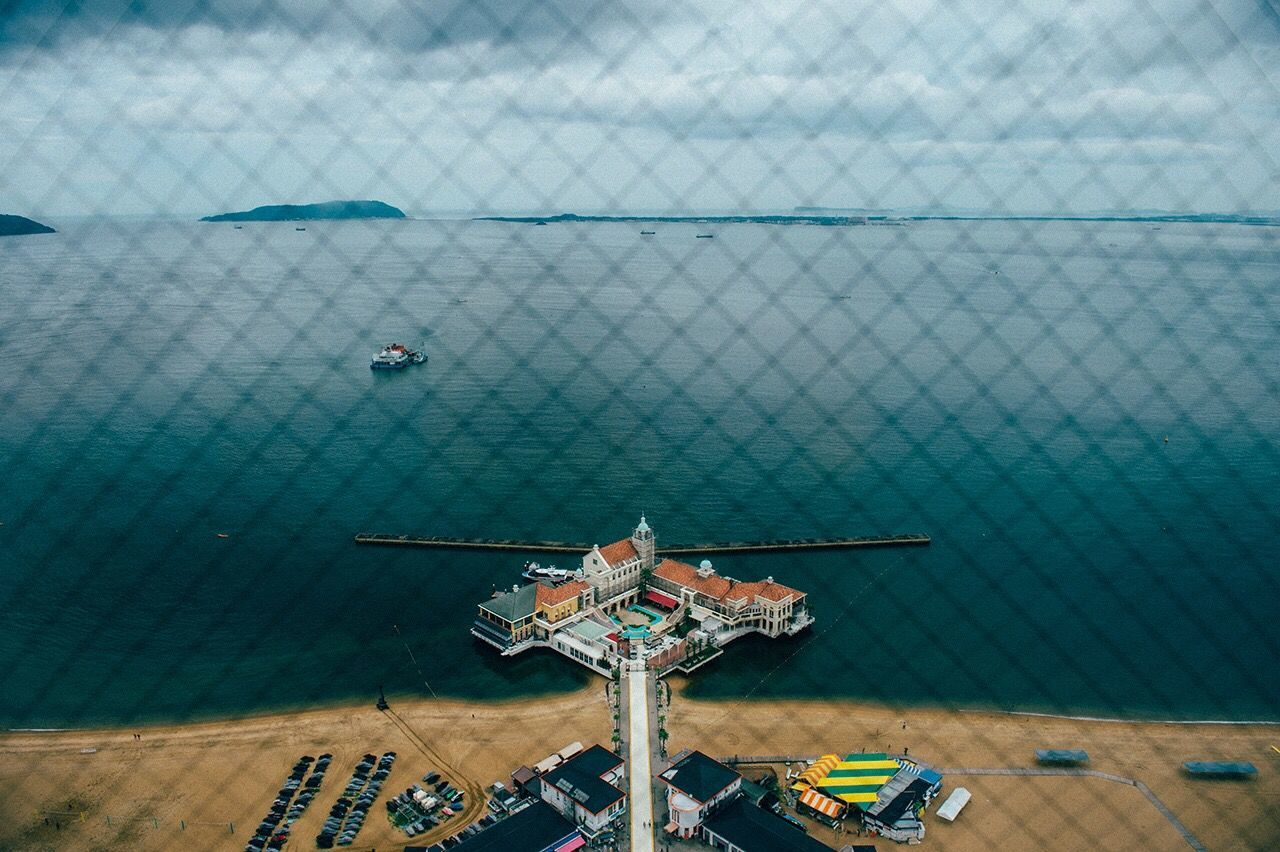 High Angle View Of Sea Seen Through Chainlink Fence