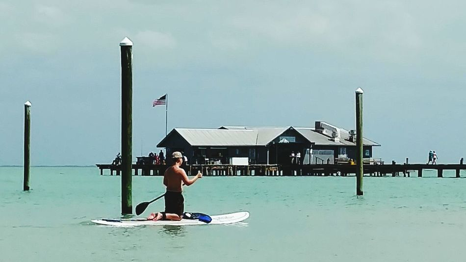Sup Stand Up Paddle Boarding Leisure Activity Leisure Time Kneeling Down Paddlingout Anna Maria Island Person Paddling People Vacation Time Having Fun Enjoying Life Salt Life Therepy Fun Turquoise Water By The Pier Surf's Up Pillars In The Water Bay Bar Bayview Sights & Views  Enjoying The View People Photography Ocean Photography