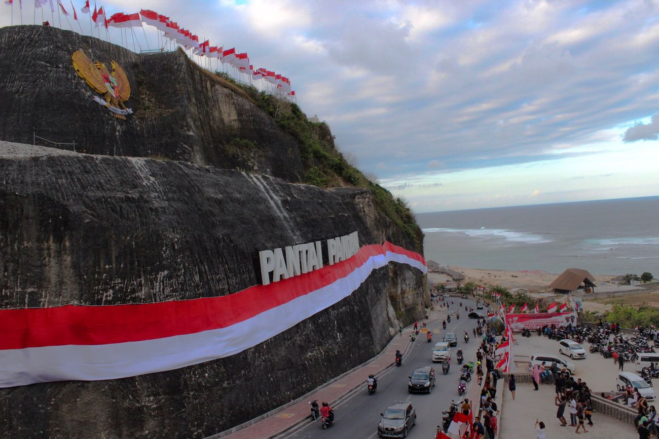 Large Group Of People Real People Outdoors Travel Destinations Built Structure Nature Beauty In Nature 17agustus Independence Day Patriotism Flags In The Wind  Pantai Pandawa Bali, Indonesia