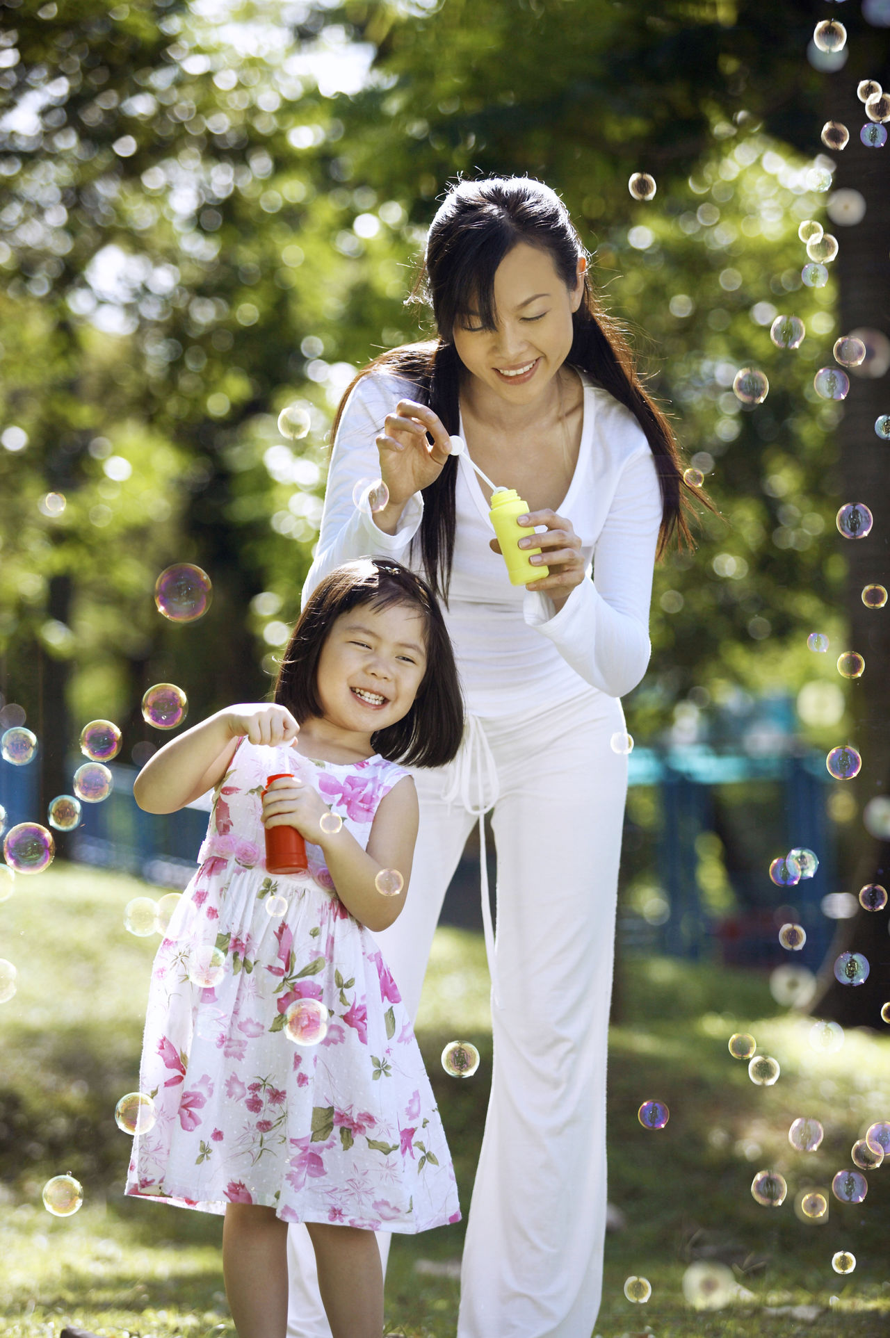 mother and daughter blowing bubbles in the park Bubble Bubble Wand Celebration Childhood Chinese Day Enjoy Family Fun Girls Holding Joy Leisure Activity Mother And Daughter Outdoors Park Pass The Time Pragnancy Recreation  Smiling Togetherness Tree Two People