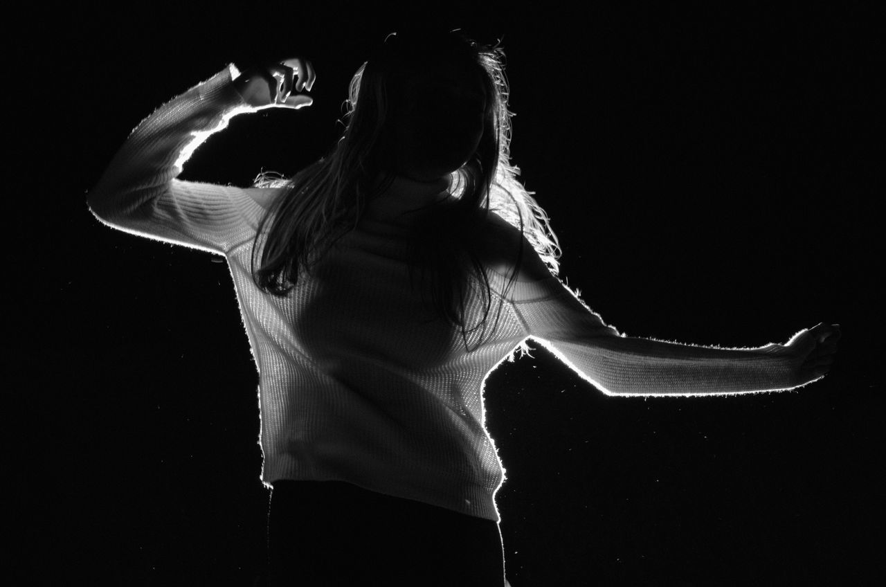 Rear View Of Woman Dancing Against Black Background