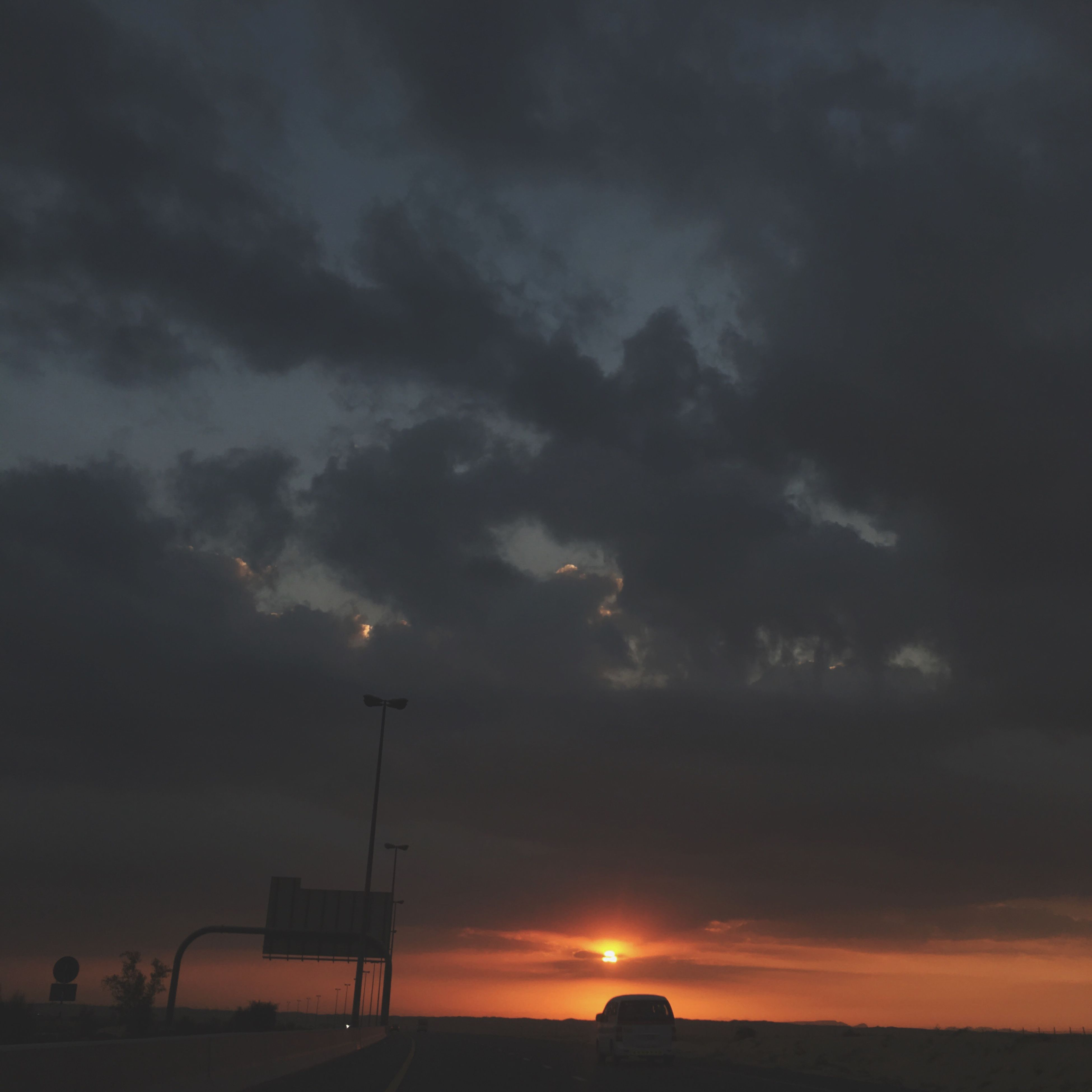 sunset, sky, cloud - sky, silhouette, scenics, beauty in nature, tranquil scene, tranquility, cloudy, orange color, nature, dramatic sky, landscape, street light, cloud, idyllic, weather, transportation, sun, outdoors