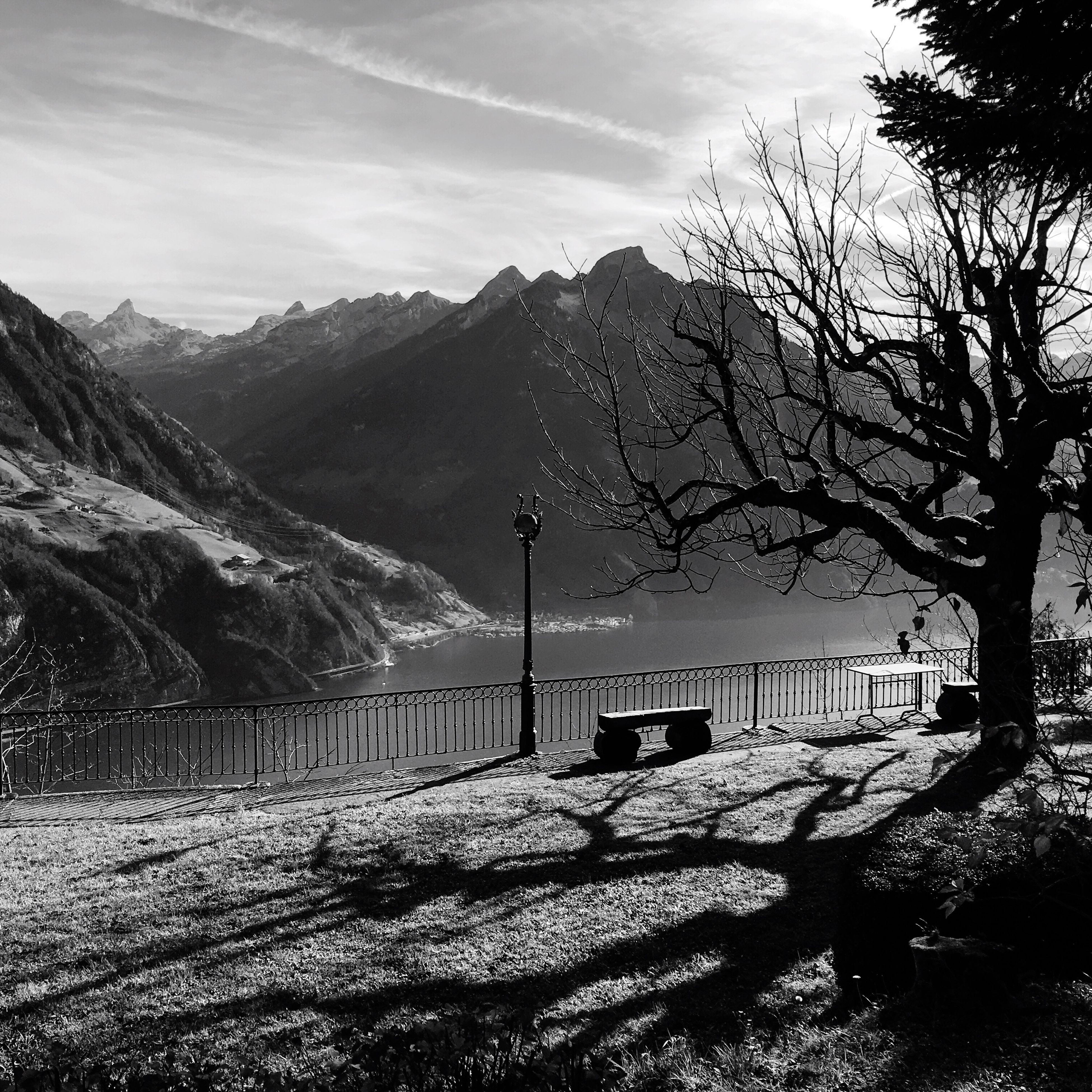 mountain, mountain range, tranquility, tranquil scene, sky, tree, scenics, landscape, beauty in nature, nature, non-urban scene, road, sunlight, railing, idyllic, remote, day, no people, outdoors, bare tree