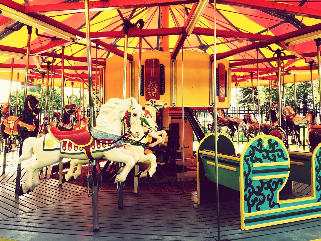 amusement park, horse, carousel, carousel horses, amusement park ride, arts culture and entertainment, animal representation, leisure activity, merry-go-round, sitting, day, outdoors, animal themes, no people