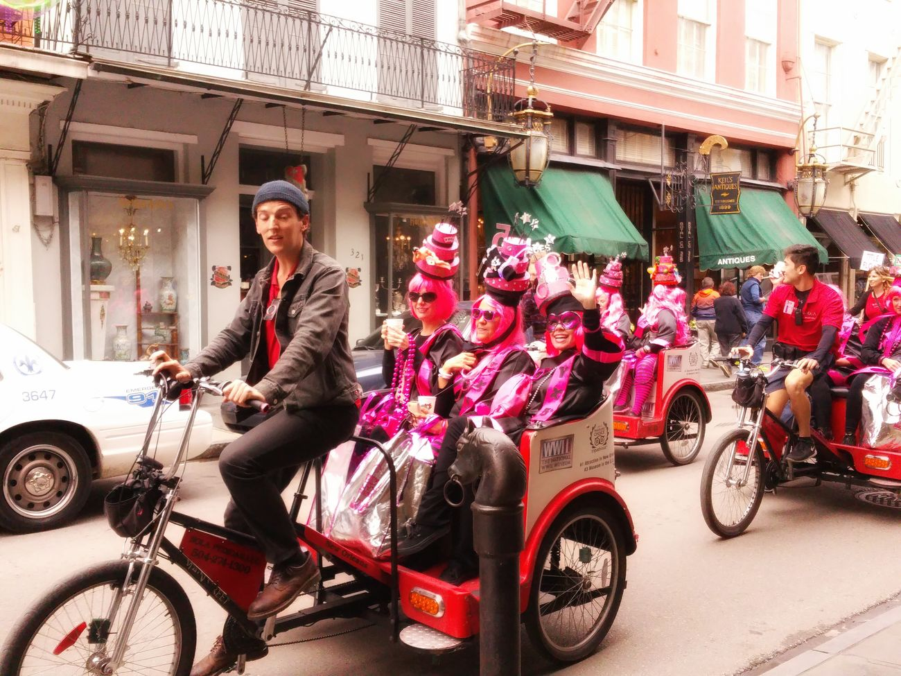 Pedicabs on Royal Street in New Orleans, LA during Mardi Gras Time Street Photography Colors Of Carnival PARADE SEASON Festive Riding Round French Quarter Pink Wig Hats Waving