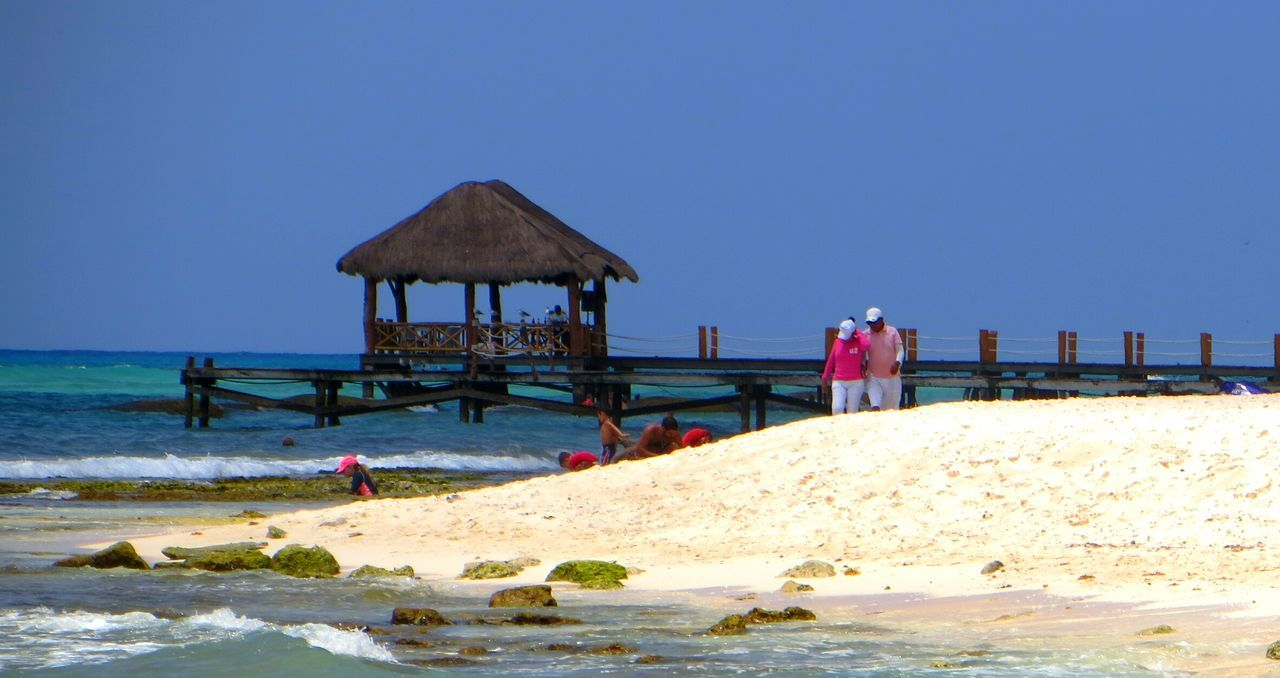 beach, clear sky, sea, sand, water, blue, thatched roof, built structure, outdoors, day, nature, architecture, sky, beauty in nature, scenics, horizon over water, real people, building exterior, wave, men, one person, people