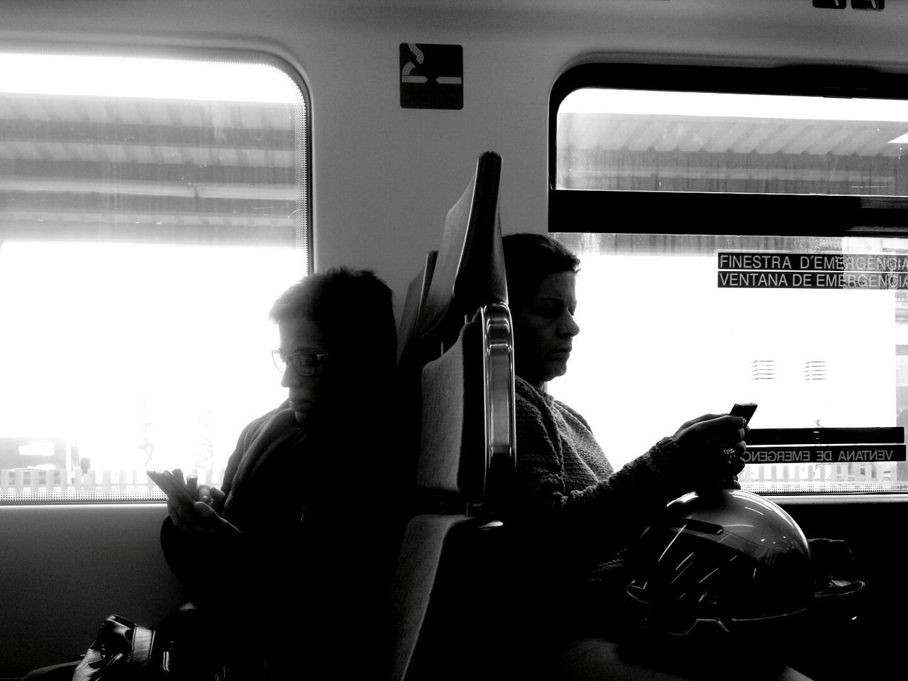 sitting, transportation, real people, public transportation, two people, mode of transport, train - vehicle, young adult, communication, casual clothing, wireless technology, travel, lifestyles, indoors, men, land vehicle, technology, holding, young men, togetherness, subway train, day, city, adult, people
