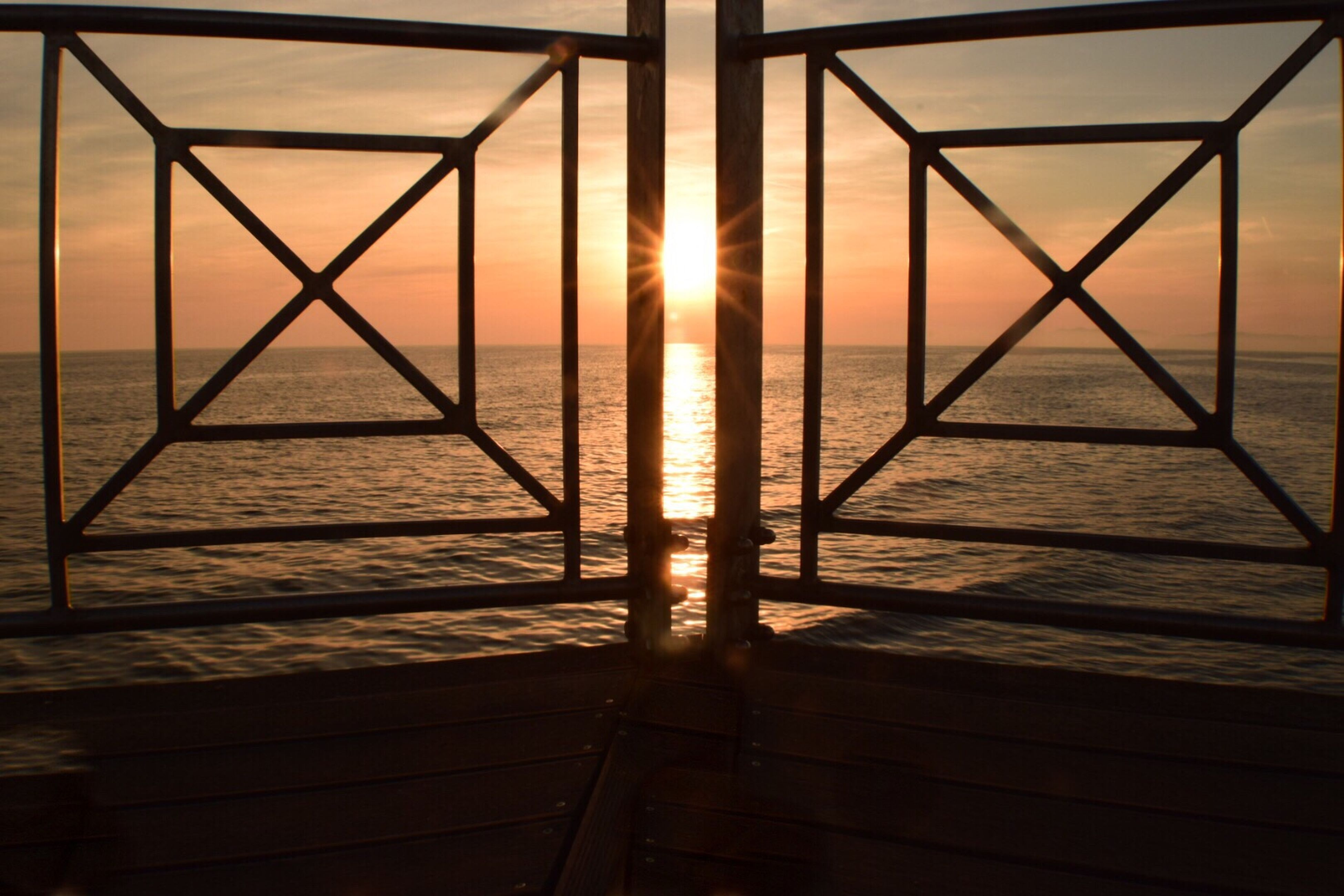 sunset, sun, orange color, sea, sunlight, water, sky, horizon over water, tranquility, silhouette, scenics, beauty in nature, railing, fence, tranquil scene, safety, nature, protection, idyllic, metal
