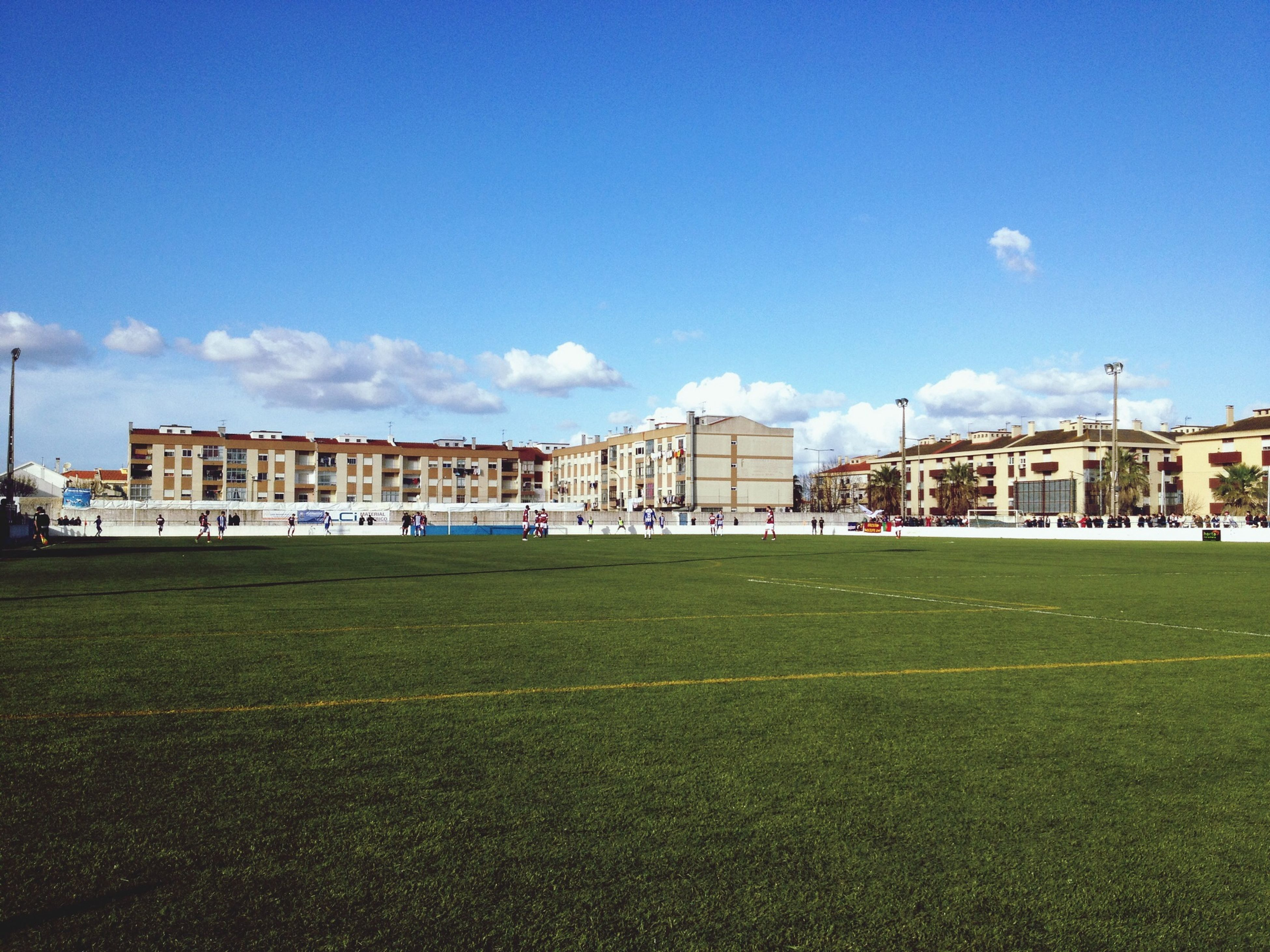 building exterior, architecture, grass, built structure, blue, sky, green color, field, grassy, cloud - sky, day, lawn, cloud, copy space, outdoors, incidental people, house, mid distance, nature, city