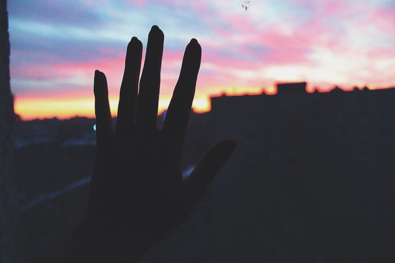 Cropped Silhouette Hand Of Person At Sunset