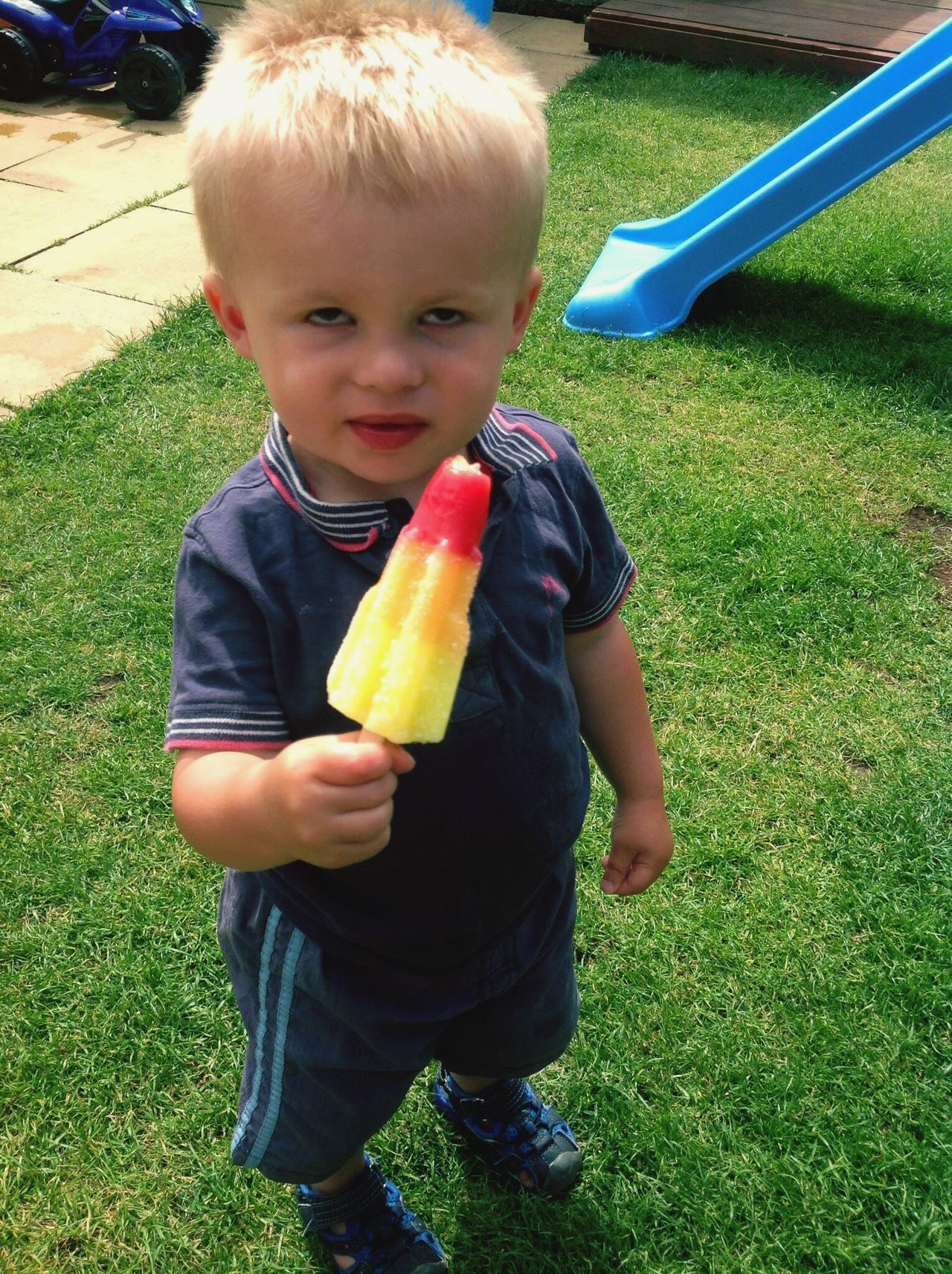 Frozen Food Food And Drink Eating Flavored Ice Childhood Grass One Person Ice Cream Sweet Food Holding Innocence Elementary Age Front View Summer Outdoors Indulgence Blond Hair Leisure Activity Refreshment Real People