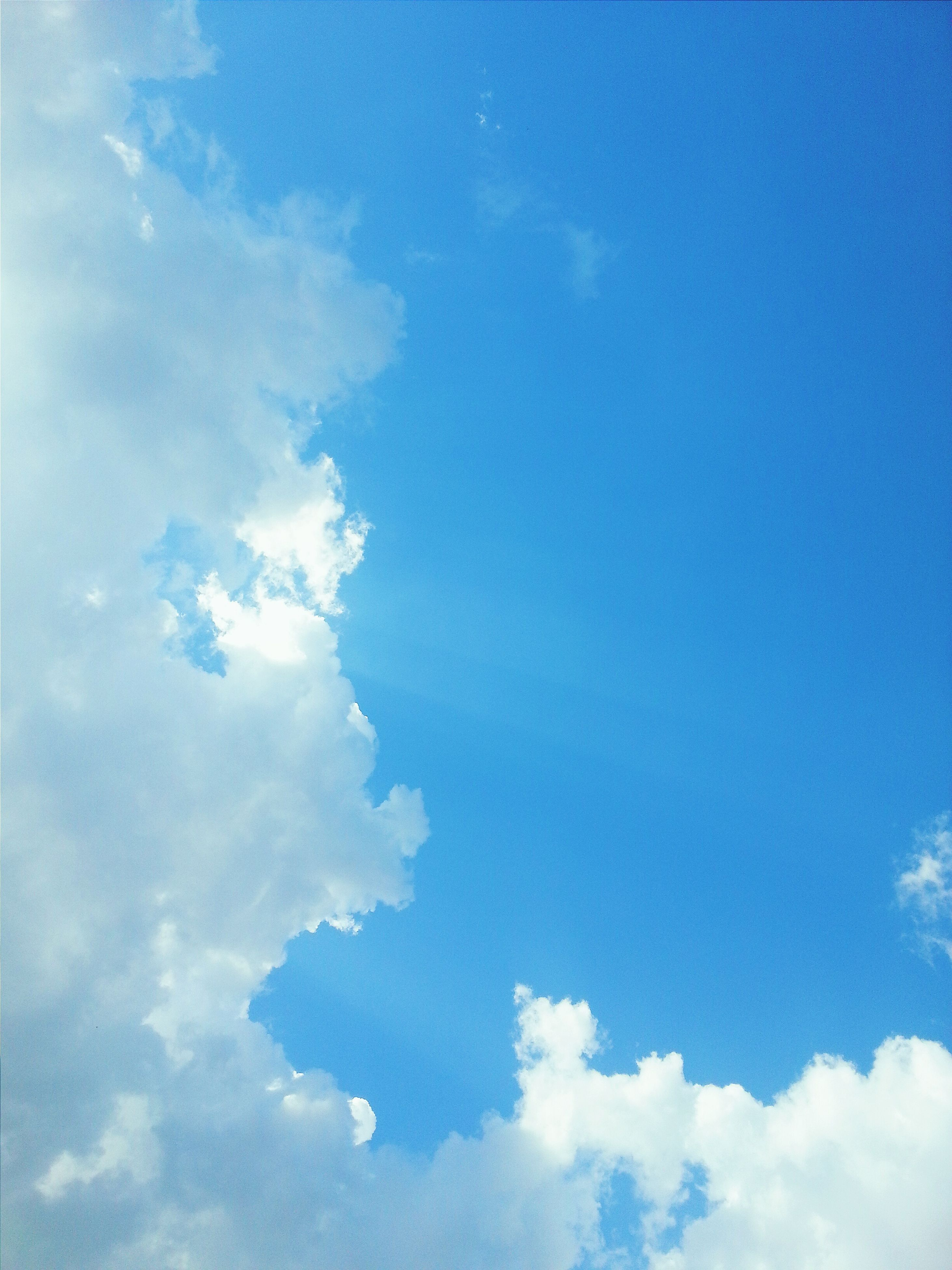 blue, low angle view, sky, beauty in nature, sky only, cloud - sky, tranquility, scenics, nature, tranquil scene, cloud, backgrounds, idyllic, white color, cloudscape, outdoors, day, no people, full frame, cloudy