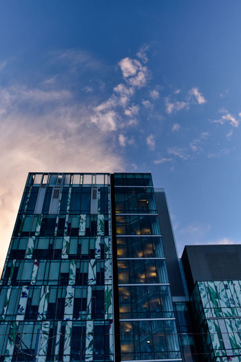 low angle view of office building with patterned walls and glass stairwell against sky Architecture Building Exterior Built Structure City Decorated Wall Glass Stairwell Growth Low Angle View Modern No People Outdoors Pattern Sky Skyscraper Sunset Behind Building Window