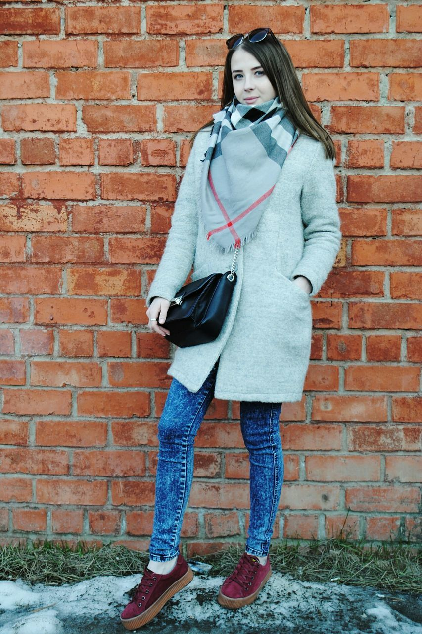 brick wall, standing, one person, full length, casual clothing, looking at camera, portrait, front view, leaning, jeans, young adult, day, beautiful woman, hands in pockets, hooded shirt, cold temperature, fashion, one young woman only, winter, outdoors, young women, one woman only, real people, beauty, adult, warm clothing, adults only, people