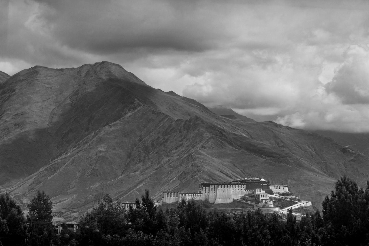 Potala Palace By Mountains Against Cloudy Sky