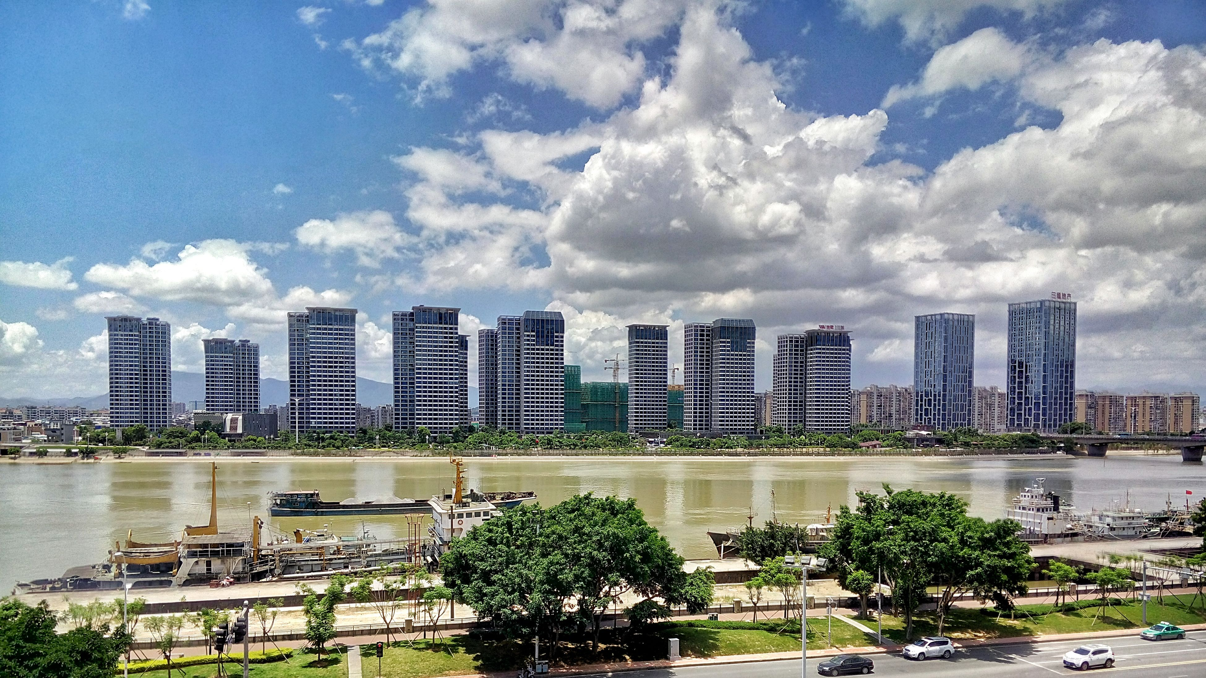 architecture, building exterior, built structure, city, water, sky, skyscraper, modern, waterfront, tall - high, cloud - sky, building story, river, travel destinations, tower, growth, development, reflection, city life, cloud, urban skyline, day, office building, outdoors, wide shot, riverbank, water surface, cloudy