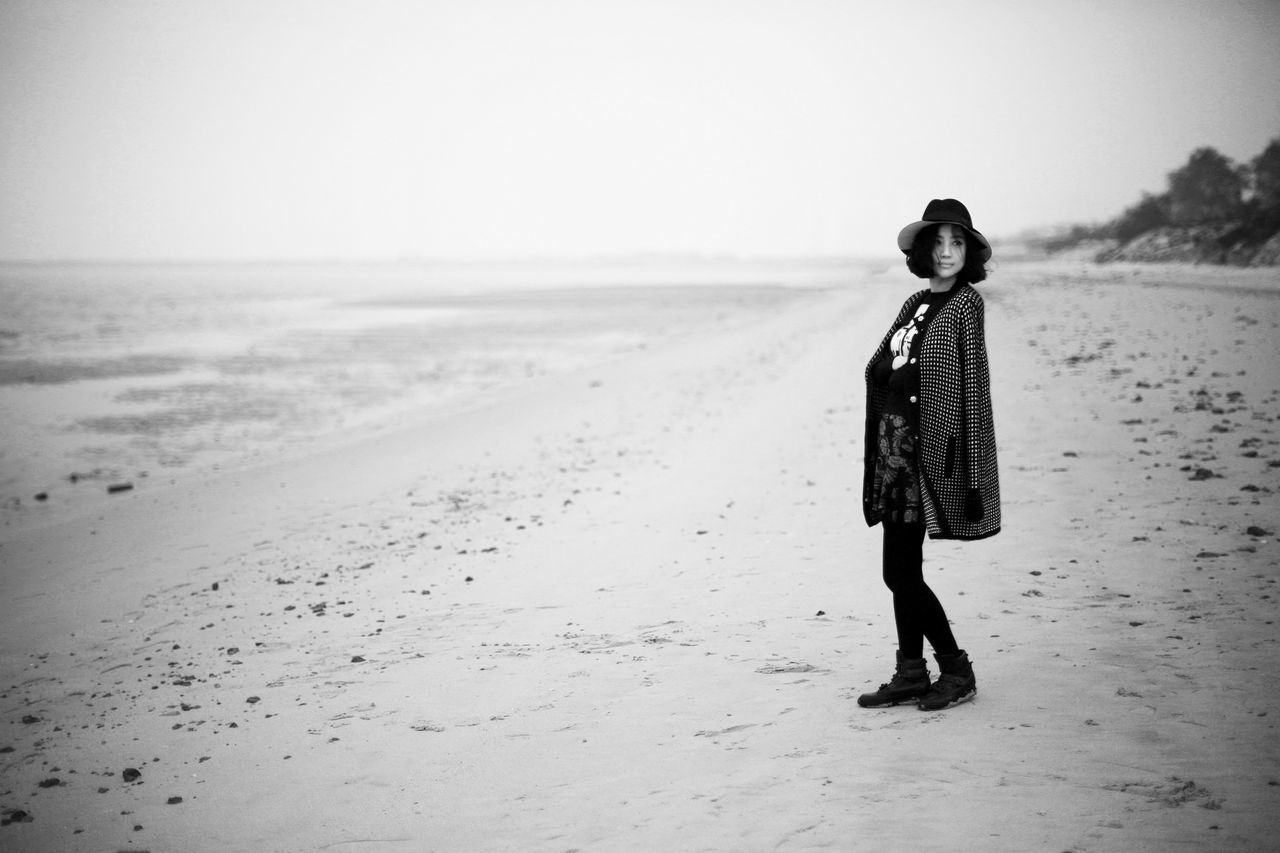 beach, sand, sea, full length, one person, shore, horizon over water, real people, clear sky, nature, tranquil scene, outdoors, scenics, sky, rear view, beauty in nature, walking, standing, day, tranquility, water, lifestyles, women, landscape, young women, young adult, warm clothing, people