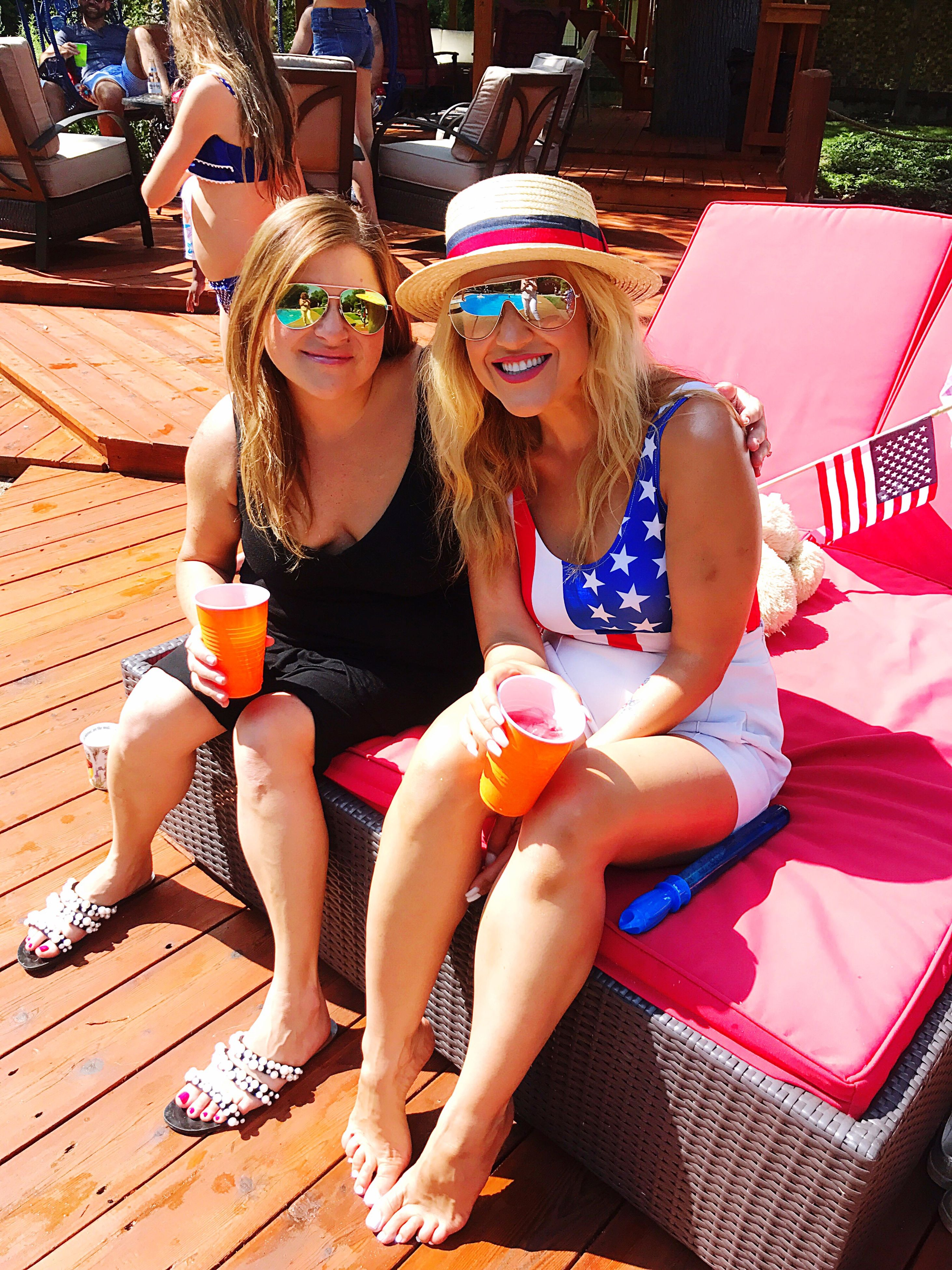 sunglasses, sitting, leisure activity, food and drink, drinking, togetherness, two people, drink, real people, front view, summer, day, outdoors, disposable cup, communication, bonding, lifestyles, friendship, young adult, young women, vacations, full length, smiling, ice cream, technology, selfie, frozen food