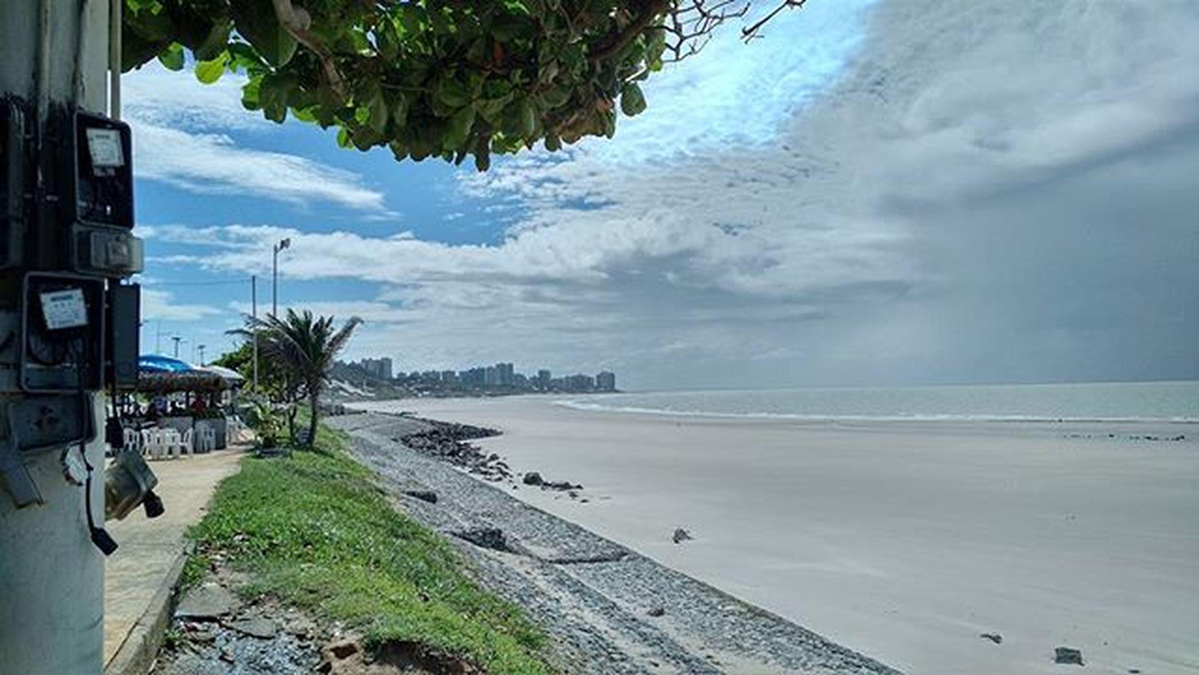 sea, beach, sky, water, tree, horizon over water, shore, palm tree, cloud - sky, sand, scenics, nature, tranquility, beauty in nature, tranquil scene, cloudy, cloud, coastline, incidental people, day