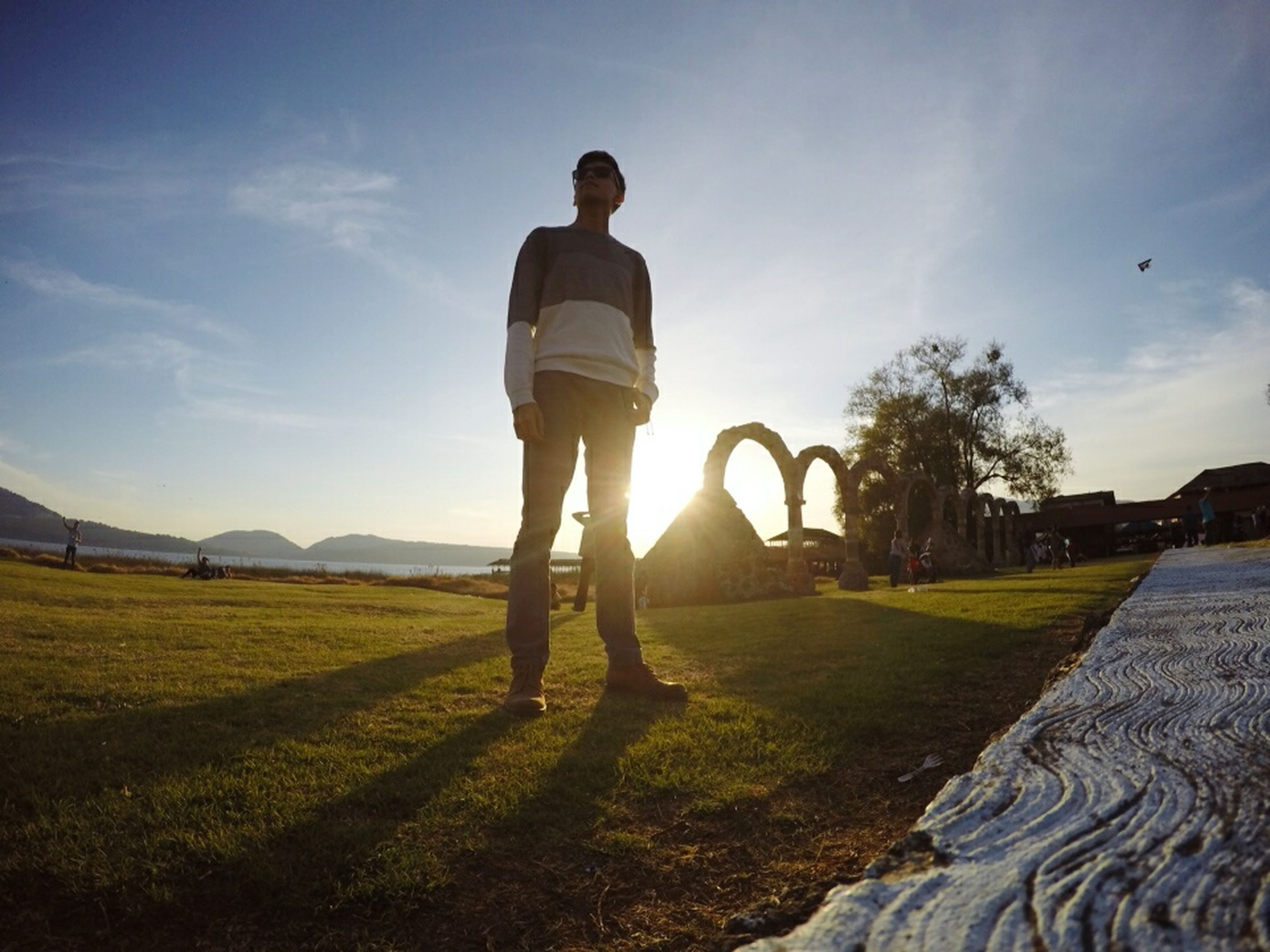 full length, lifestyles, sky, leisure activity, casual clothing, rear view, sunlight, grass, standing, landscape, field, men, walking, sun, person, nature, tranquility, tranquil scene