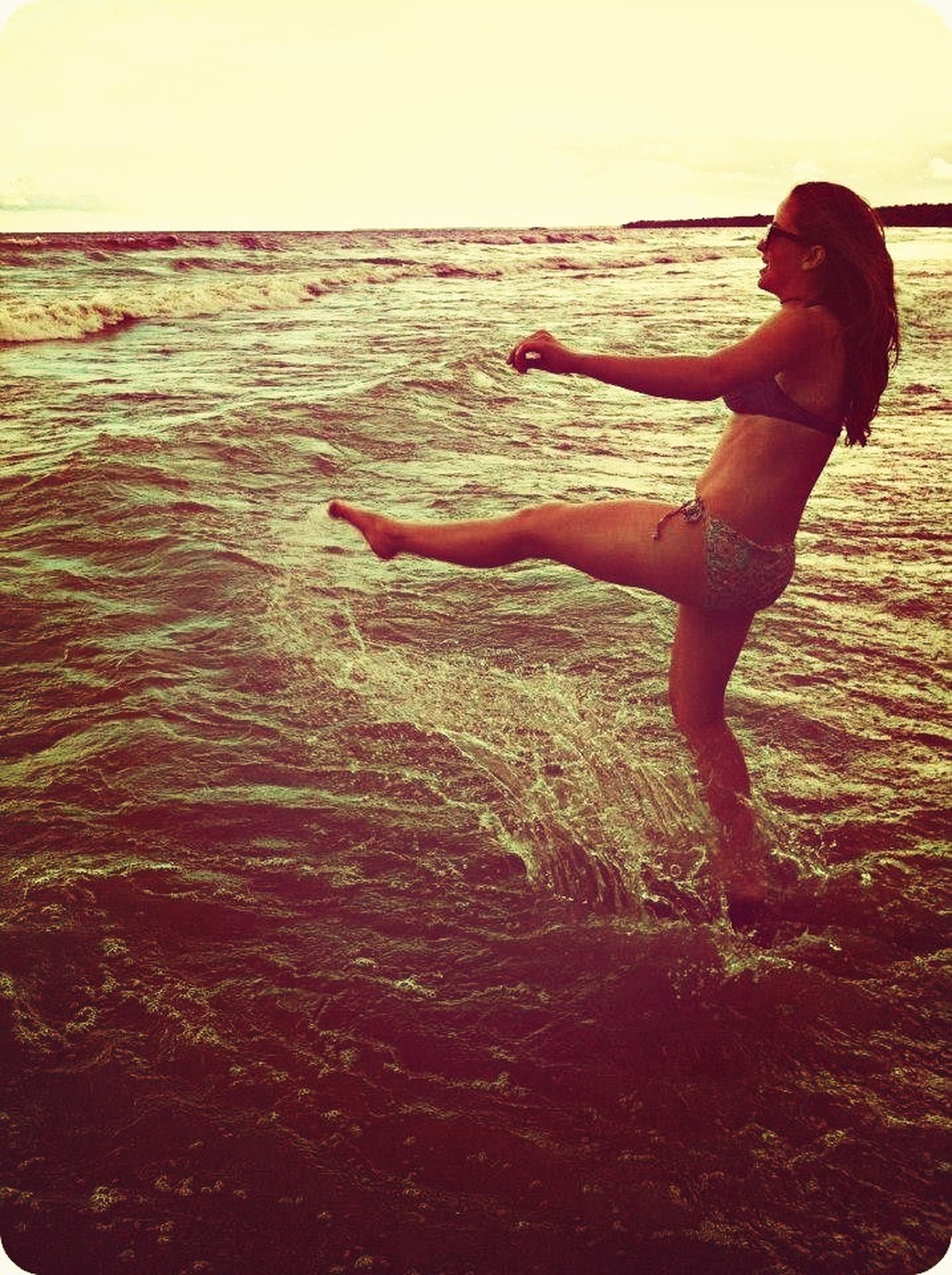 lifestyles, leisure activity, full length, young adult, casual clothing, standing, young women, person, arms outstretched, enjoyment, side view, carefree, fun, holding, sunset, arms raised, mid-air, skill