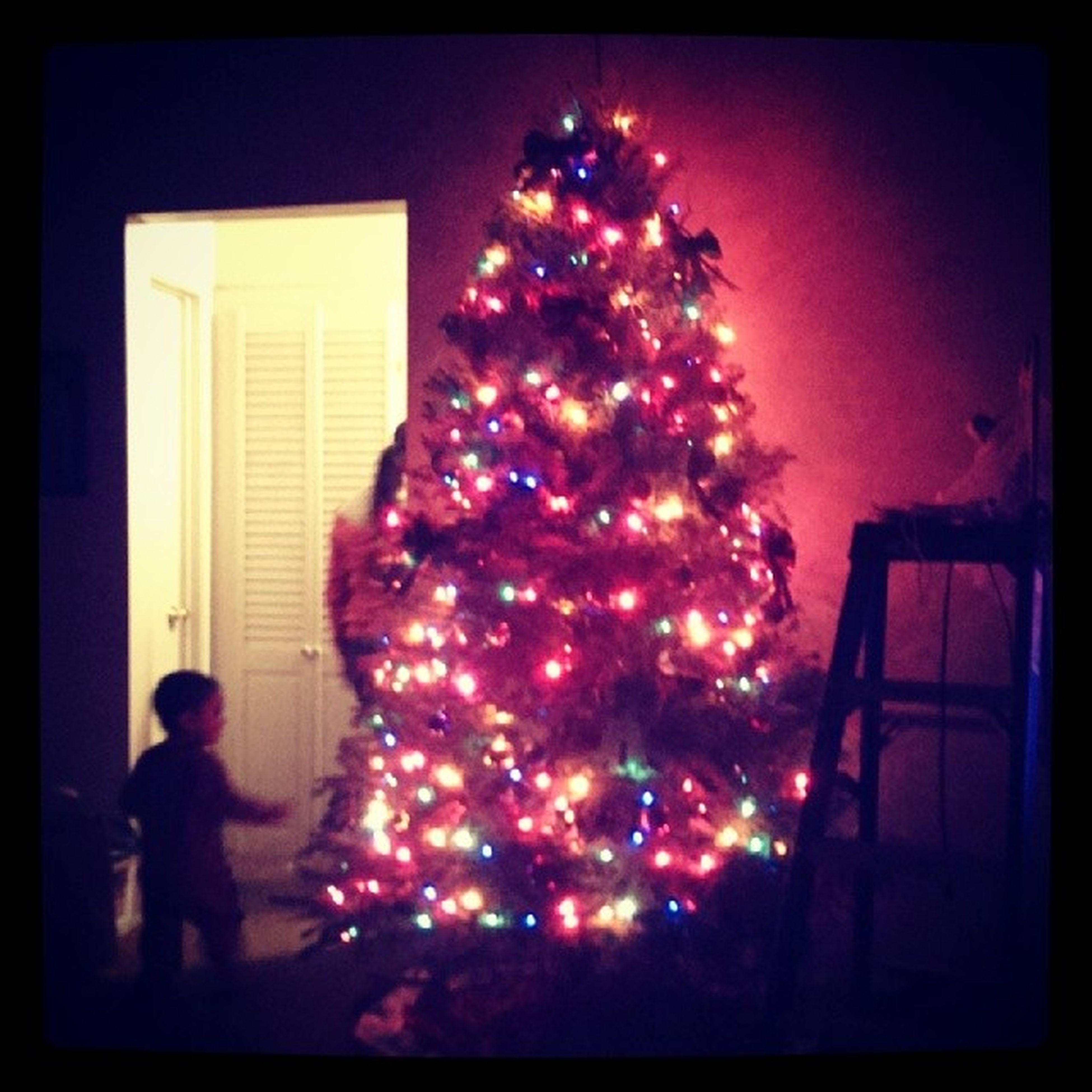 indoors, illuminated, transfer print, celebration, auto post production filter, night, lifestyles, christmas, decoration, leisure activity, christmas decoration, window, arts culture and entertainment, red, person, christmas tree, lighting equipment, glass - material
