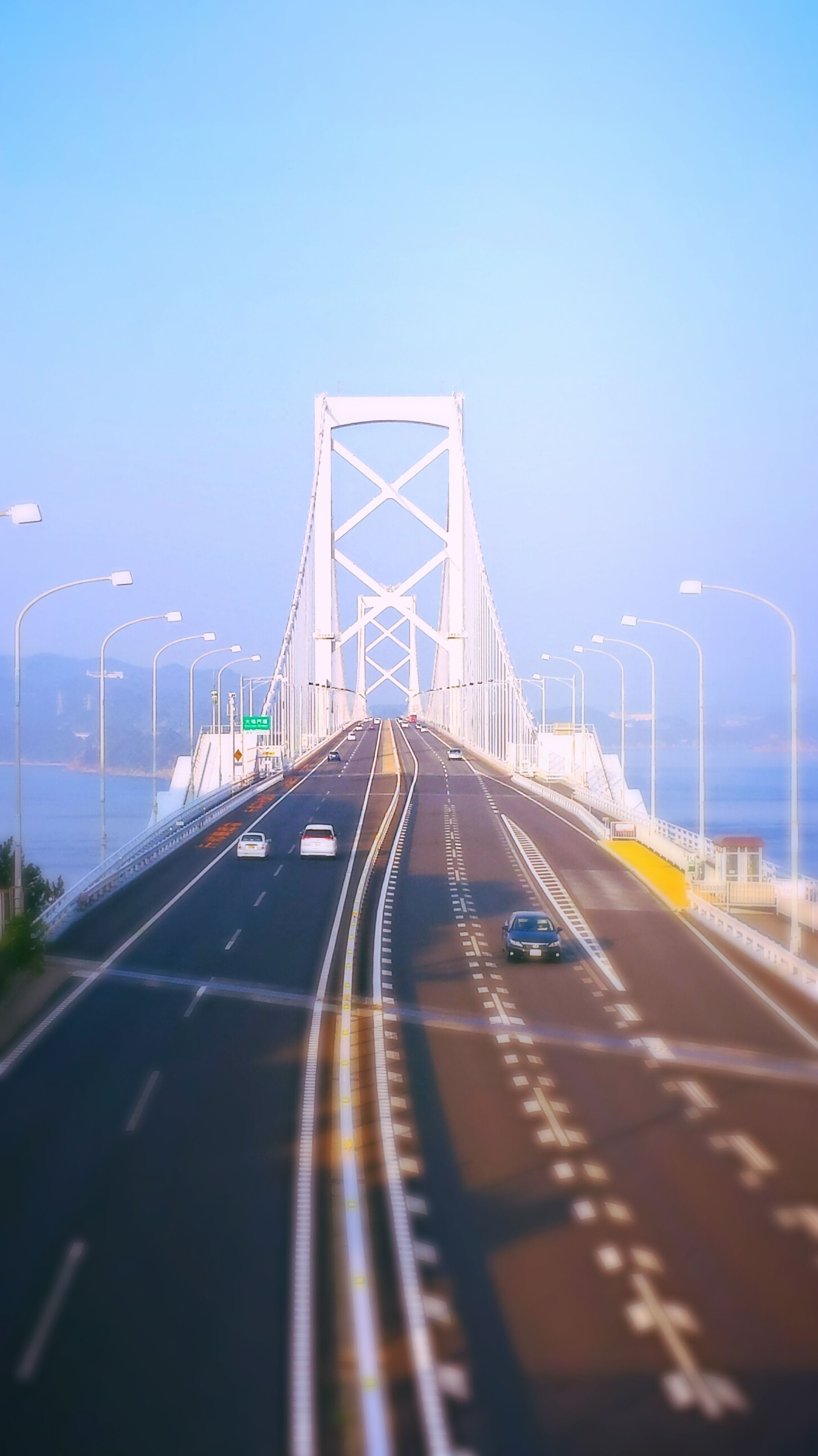 the way forward, transportation, clear sky, diminishing perspective, road, vanishing point, road marking, copy space, blue, street light, built structure, connection, empty, long, architecture, street, surface level, car, sky, bridge - man made structure