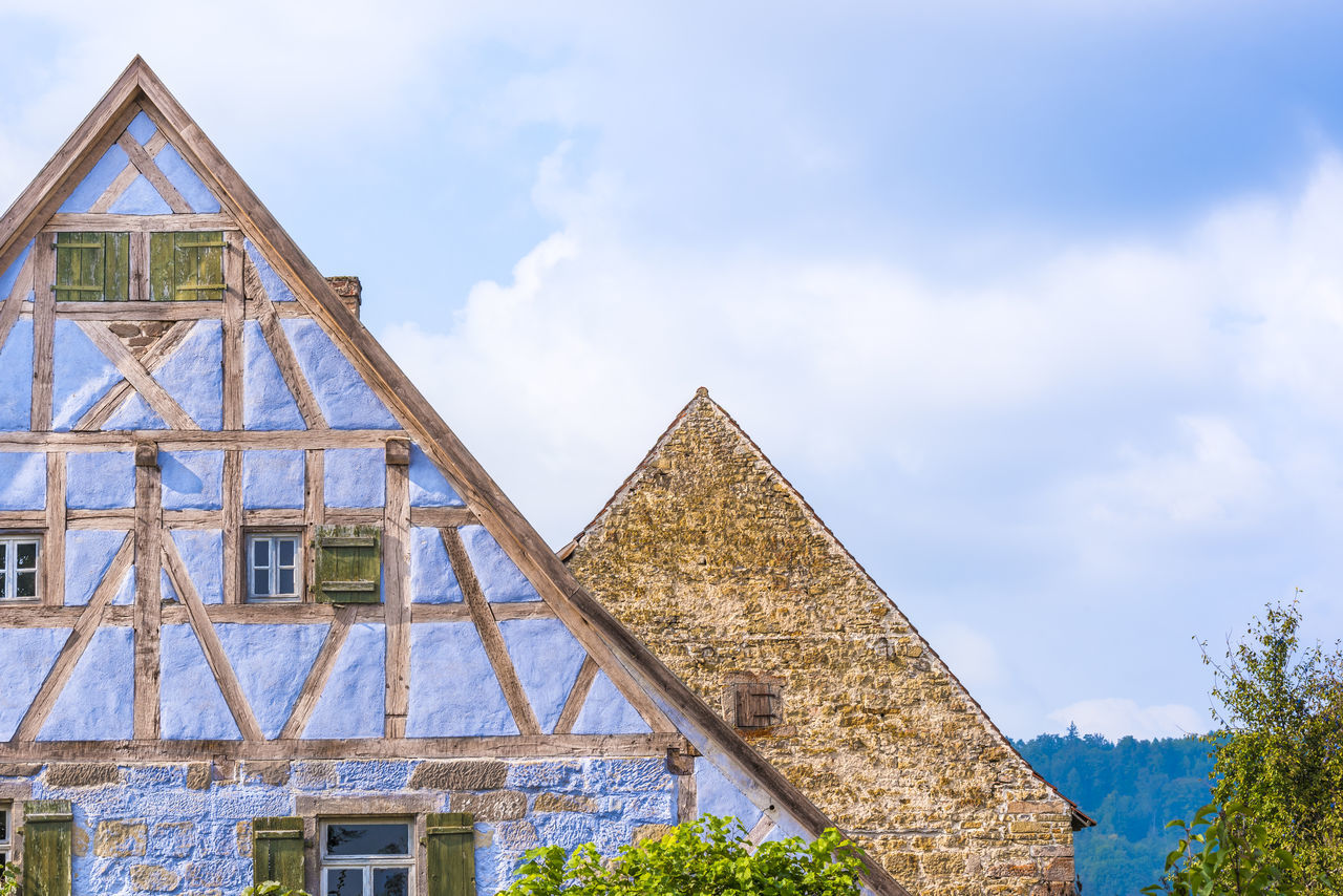 Antique German gable roofs and facades against sky - Architectural details from two medieval German houses , one with blue half timbered walls, small windows, wooden shutters and one with aged stone wall and a single wooden window. Antique Building Architecture Baden-Württemberg  Blue Sky Blue Walls Built Structure Cloud - Sky Construction Day Facade Building Gable Roof German Architecture German House Medieval Rooftops Rustic Shutters Sky Spring Swabian Timbered House