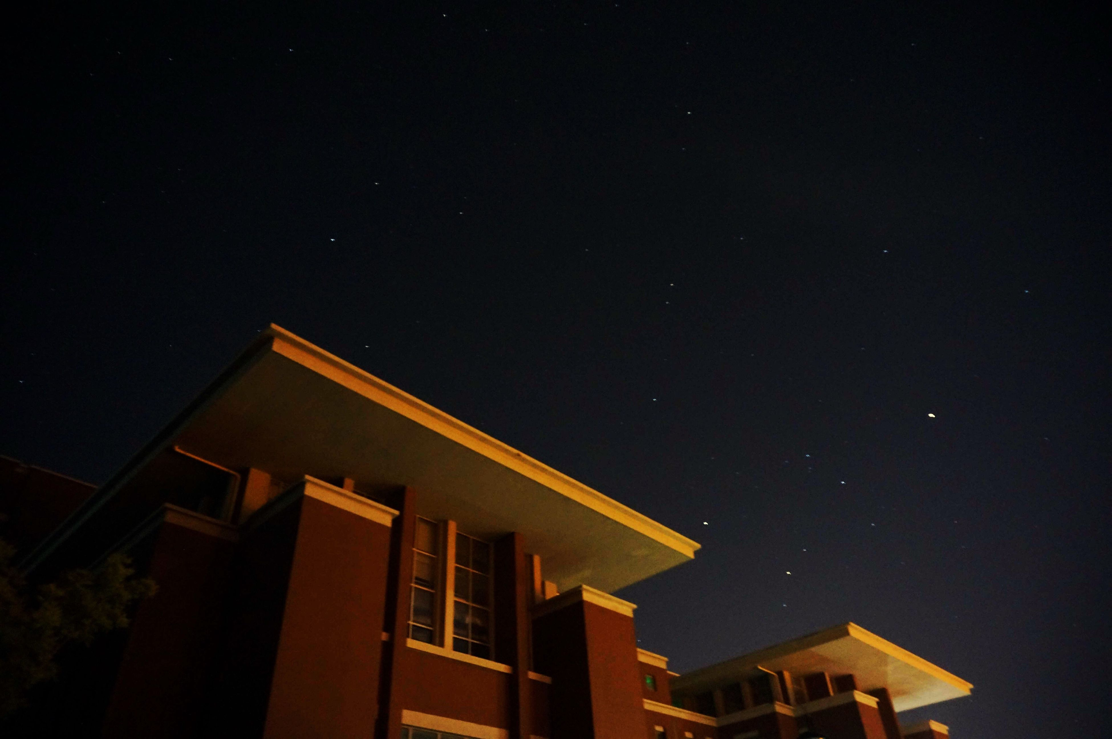 architecture, night, built structure, building exterior, low angle view, copy space, illuminated, clear sky, sky, moon, house, building, high section, dark, residential structure, residential building, outdoors, no people, city, nature
