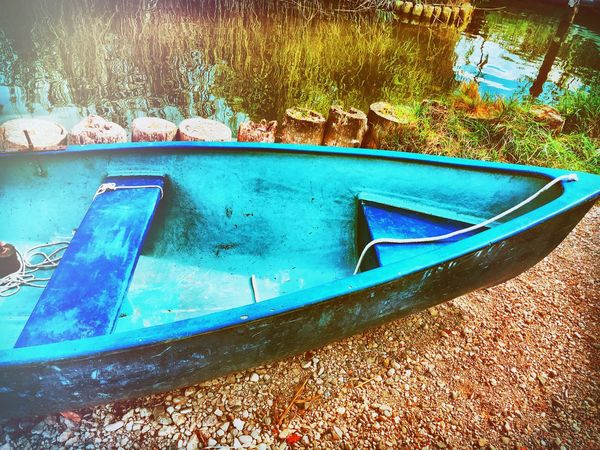 Transportation Nautical Vessel Boat Mode Of Transport Moored Blue Weathered Messy Plant Day Outdoors Tranquility Nature Gravel Riverbank No People Shore Tranquil Scene
