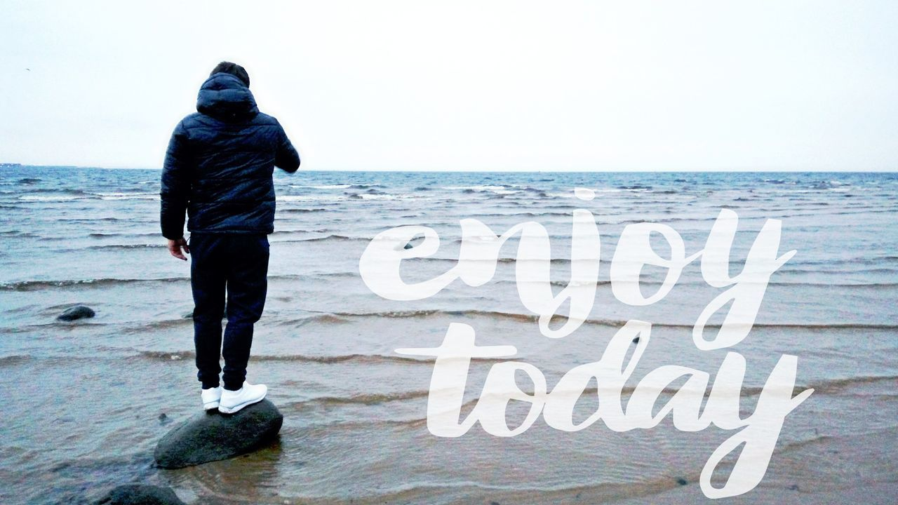 sea, horizon over water, water, text, nature, scenics, standing, tranquil scene, one person, outdoors, leisure activity, beauty in nature, full length, lifestyles, real people, beach, day, communication, vacations, men, sky, clear sky, people