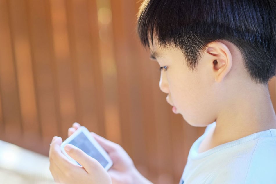 Side view of young kid using mobile device Boy Close-up Communication Day Device East Asian Holding Kid Lifestyles Looking At Smartphone Mobile Mobile Conversations Mobile Phone Natural Light People Portrait Side View Tech Technology Using Smartphone Young