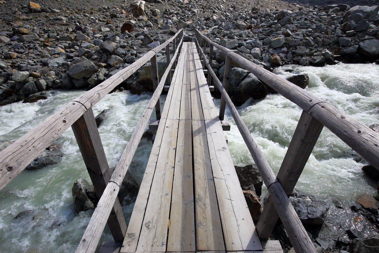 Wooden brigdge over glacier river. Architecture Barren Bridge Bridge - Man Made Structure Connection Crossing The River Diminishing Perspective Engadin Beautifully Organized EyeEm Best Shots EyeEm Nature Lover Getting Inspired Glacier River Hiking Lines Minimalism Perspective River Rocks And Water Rough Simple The Way Forward Water Wild Wood