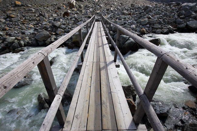 Wooden brigdge over glacier river. Architecture Barren Bridge Bridge - Man Made Structure Connection Crossing The River Diminishing Perspective Engadin Eye4photography  EyeEm Best Shots EyeEm Nature Lover Getting Inspired Glacier River Hiking Lines Minimalism Perspective River Rocks And Water Rough Simple The Way Forward Water Wild Wood