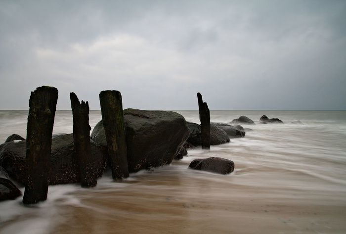 Groynes on shore of the Baltic Sea. Baltic Sea Beach Beauty In Nature Cloud - Sky Coast Coastline Groyne Horizon Horizon Over Water Kühlungsborn Nature Non-urban Scene Outdoors Rock - Object Rock Formation Scenics Sea Shore Sky Tourism Tranquil Scene Tranquility Travel Destinations Water Waterfront