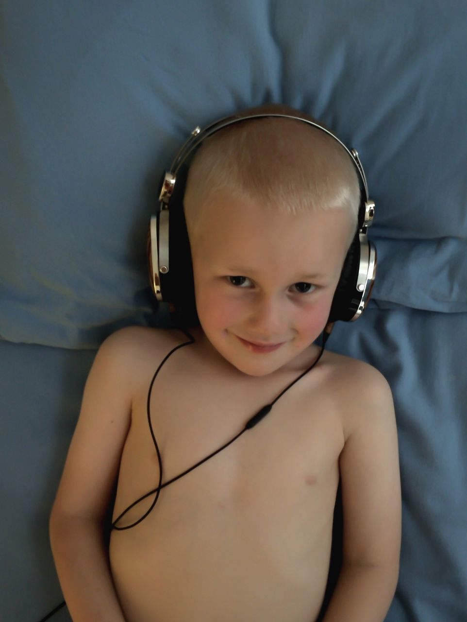 High Angle Portrait Of Smiling Shirtless Boy Wearing Headphones On Bed